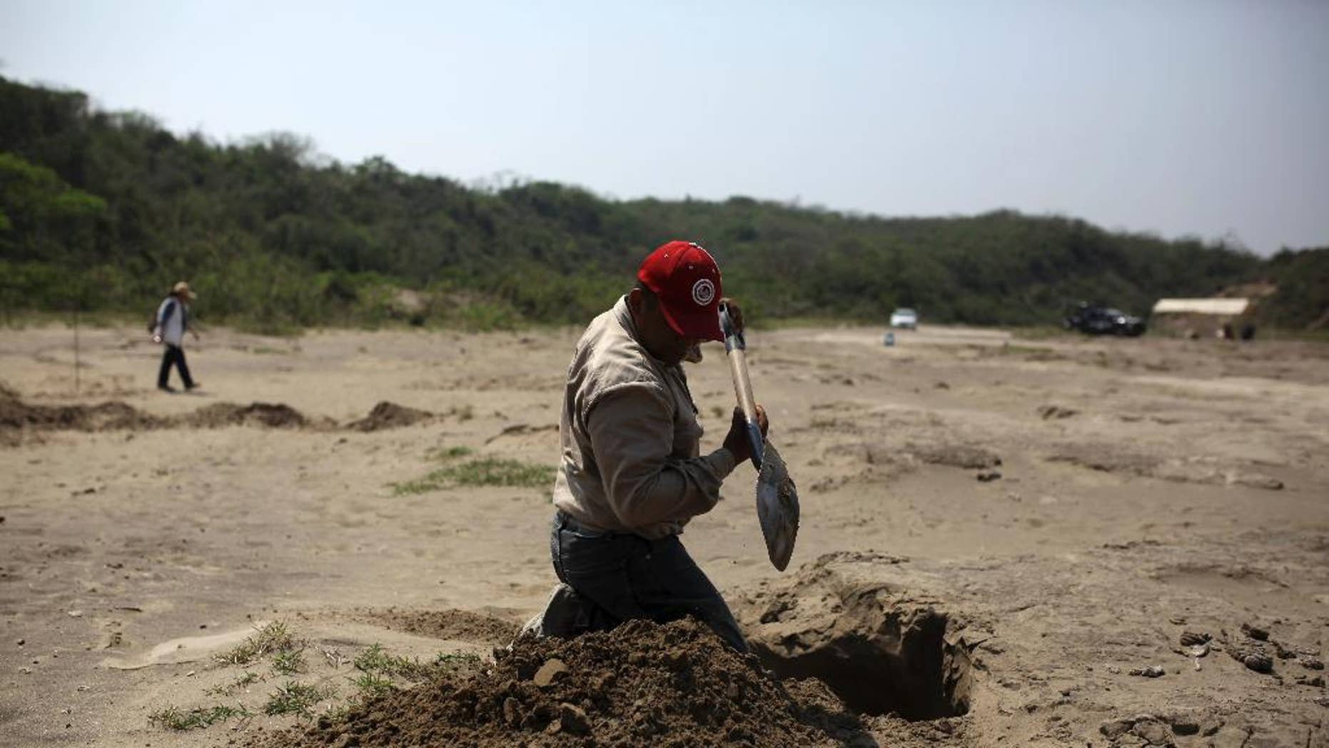 FILE - In this March 30, 2017 file photo, A volunteer searcher digs into the earth at a clandestine grave site in Colinas de Santa Fe, in Mexico's Veracruz state. Mexico's government human rights agency said Thursday that tens of thousands of people have been recorded as missing across the country over the past two decades. And thousands have been reported found in clandestine graves during the drug war of the past 10 years. But the National Human Rights Commission says the exact numbers are a mystery. (AP Photo/Felix Marquez, File)