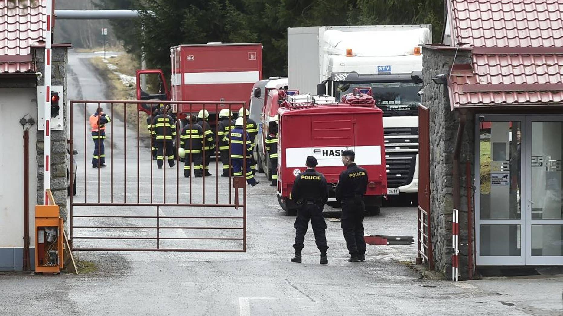 Two police officers watch over a gate as firemen stand nearby in the machinery plant Policske Strojirny where explosions have injured several people in Policka, 154 kilometers South East of Prague on Thursday, Feb. 23, 2017.  (Josef Vostarek/CTK via AP)