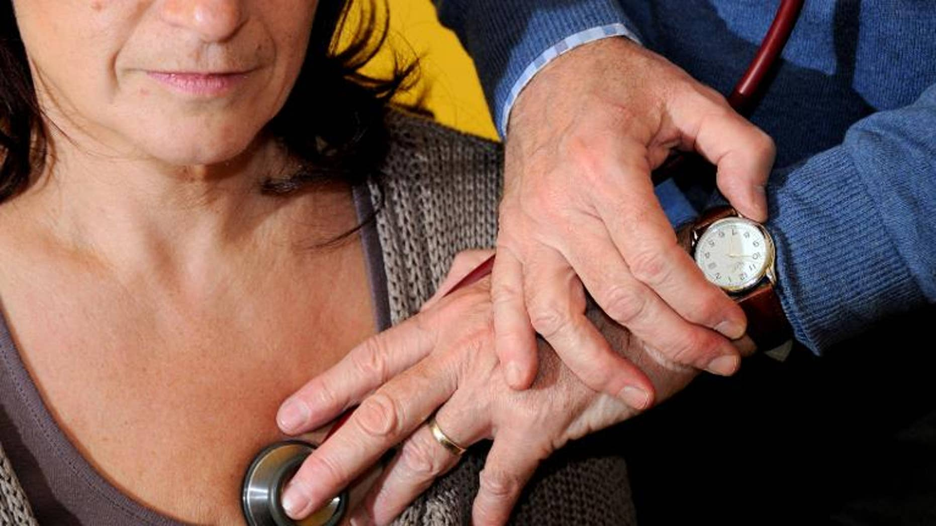 A doctor examines a patient in Godewaersvelde, northern France on September 25, 2012