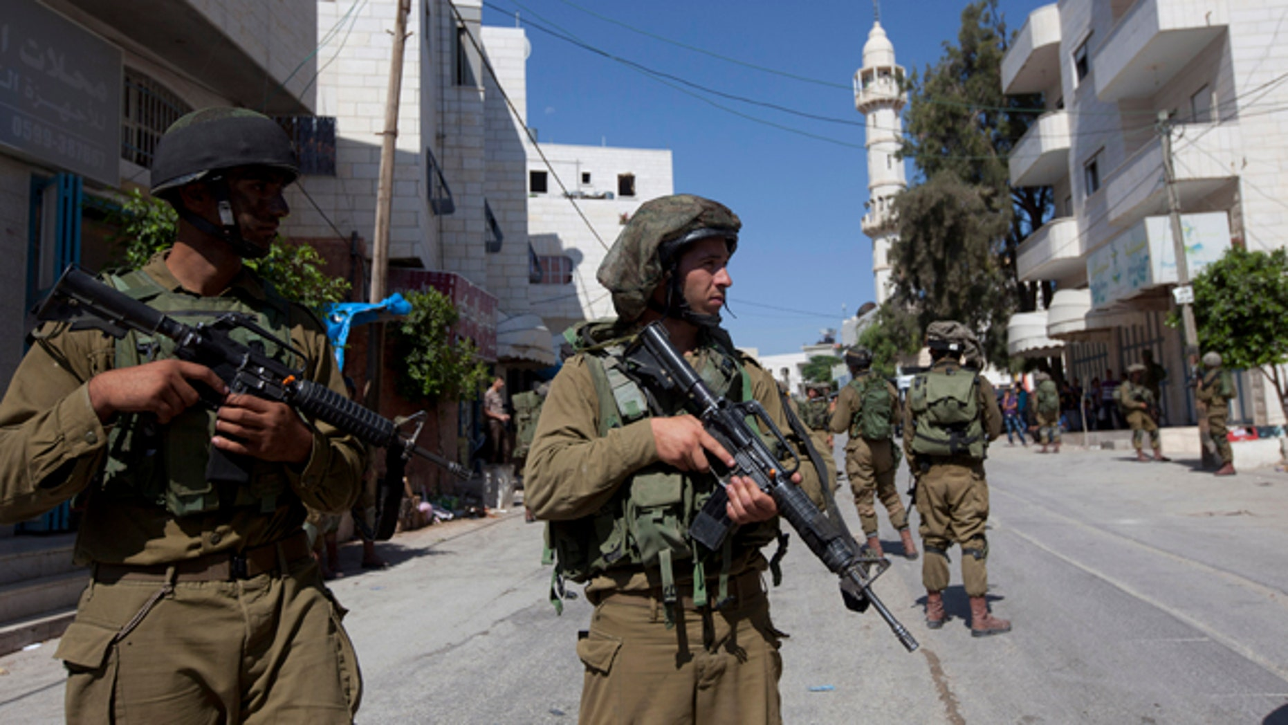 June 18, 2014: Israeli soldiers search for three missing Israeli teens believed to have been abducted in the West Bank, in the village of Taffouh near the West Bank city of Hebron. (AP/Majdi Mohammed)