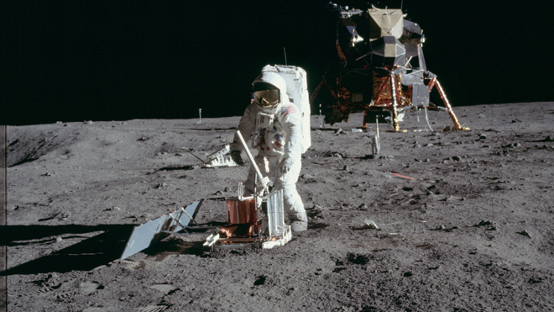 """Astronaut Edwin E. Aldrin Jr., lunar module pilot, deploys a scientific research package on the surface of the moon near the Lunar Module """"Eagle"""" during the Apollo 11 extravehicular activity (EVA) in this July 20, 1969"""
