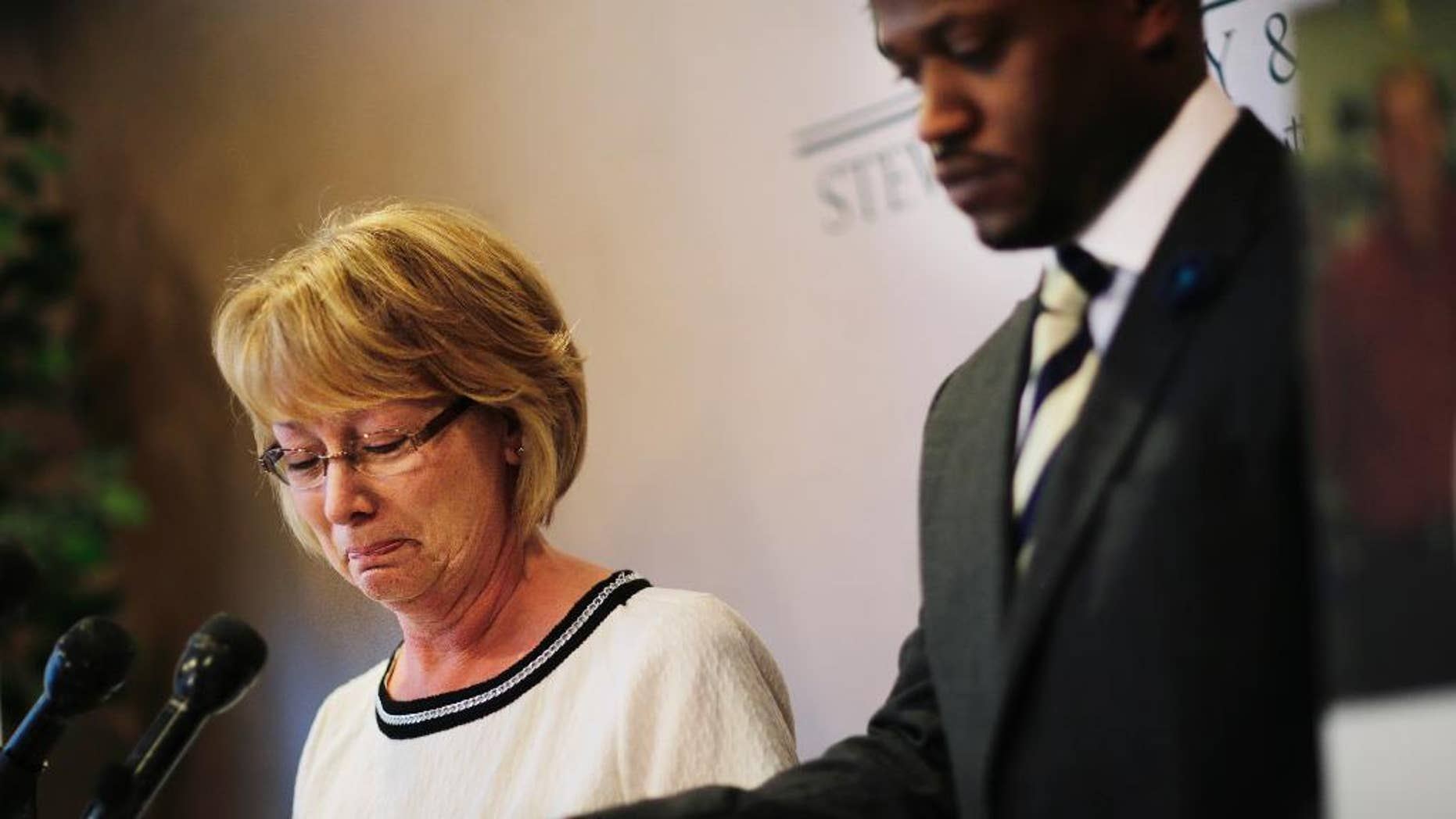 """Mary Ann Sherman, left, weeps during a news conference with her attorney Chris Stewart, right, in response to a video showing her son's struggle with police officers Friday, May 20, 2016, in Atlanta. Two deputies yell """"Stop fighting!"""" and """"He's got my Taser!"""" as they repeatedly stun Chase Sherman, handcuffed in the back of a vehicle, commanding him to relax even as he insists """"I'm dead,"""" shortly before he stops breathing, body-camera video from the incident shows. The video shows the Nov. 20 incident in the back of an SUV in Coweta County, outside Atlanta. Sherman, 32, of Destin, Florida, was pronounced dead at a hospital later that day.(AP Photo/David Goldman)"""