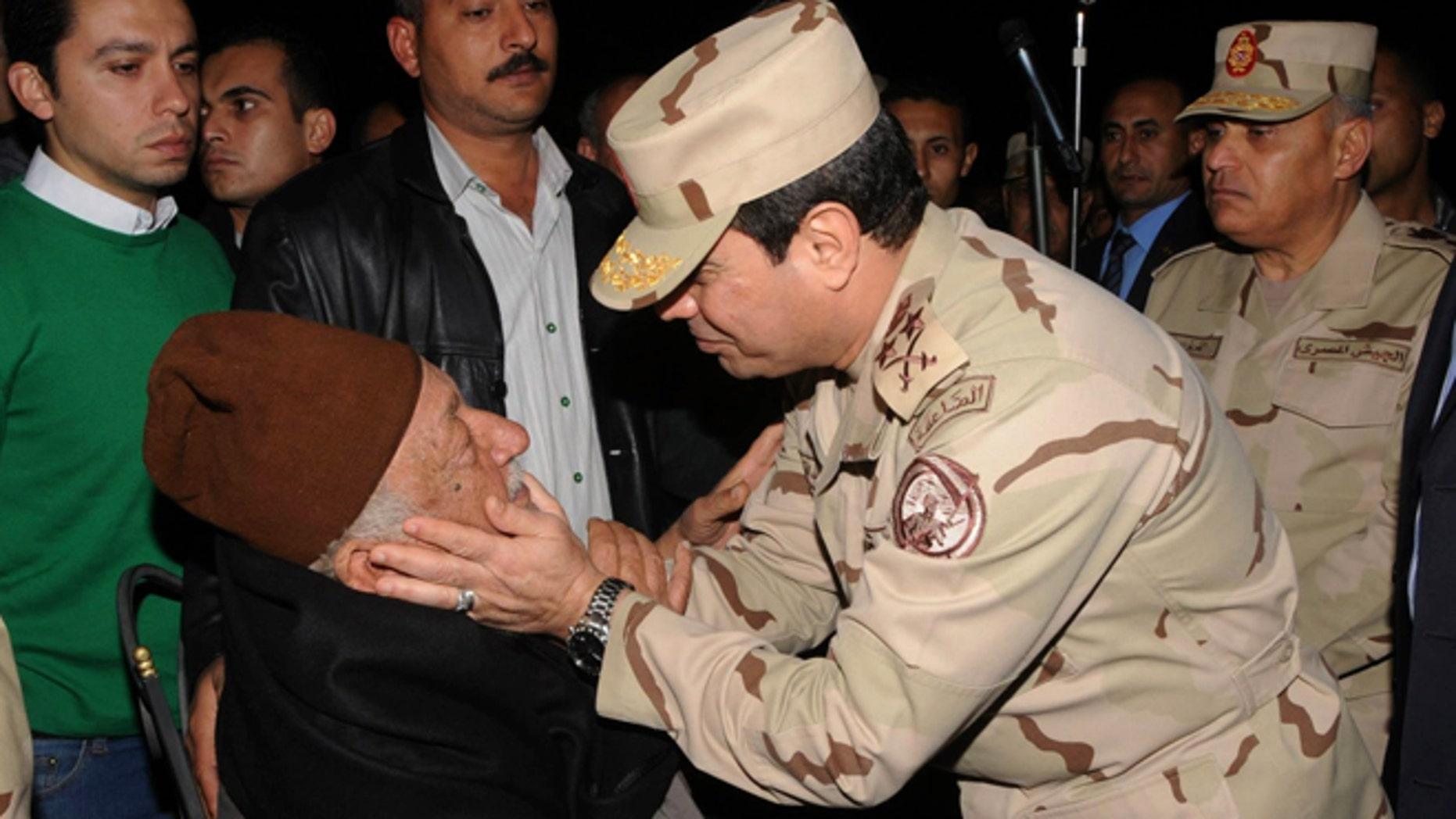 In this undated photo released by the Egyptian Defense Ministry, Defense Minister Gen. Abdel-Fattah el-Sissi consoles a man at a funeral for several military personnel who were killed when a  helicopter crashed in the Sinai Peninsula, at an undisclosed location in Egypt.