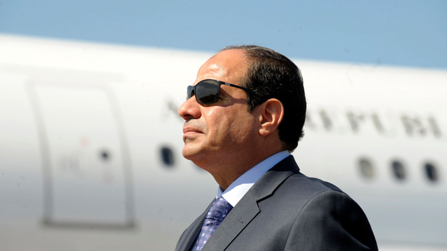 """FILE - In this June 25, 2014, file photo, Egyptian President Abdel-Fattah el-Sissi stands at Algiers airport on his arrival to Algiers, Algeria. News that Egypt's parliament speaker and his two deputies are using state funds to get cars worth hundreds of thousands of dollars has sparked a furor days after the president said Egypt was """"poor, very, very poor."""" (AP Photo/Sidali Djarboub, File)"""