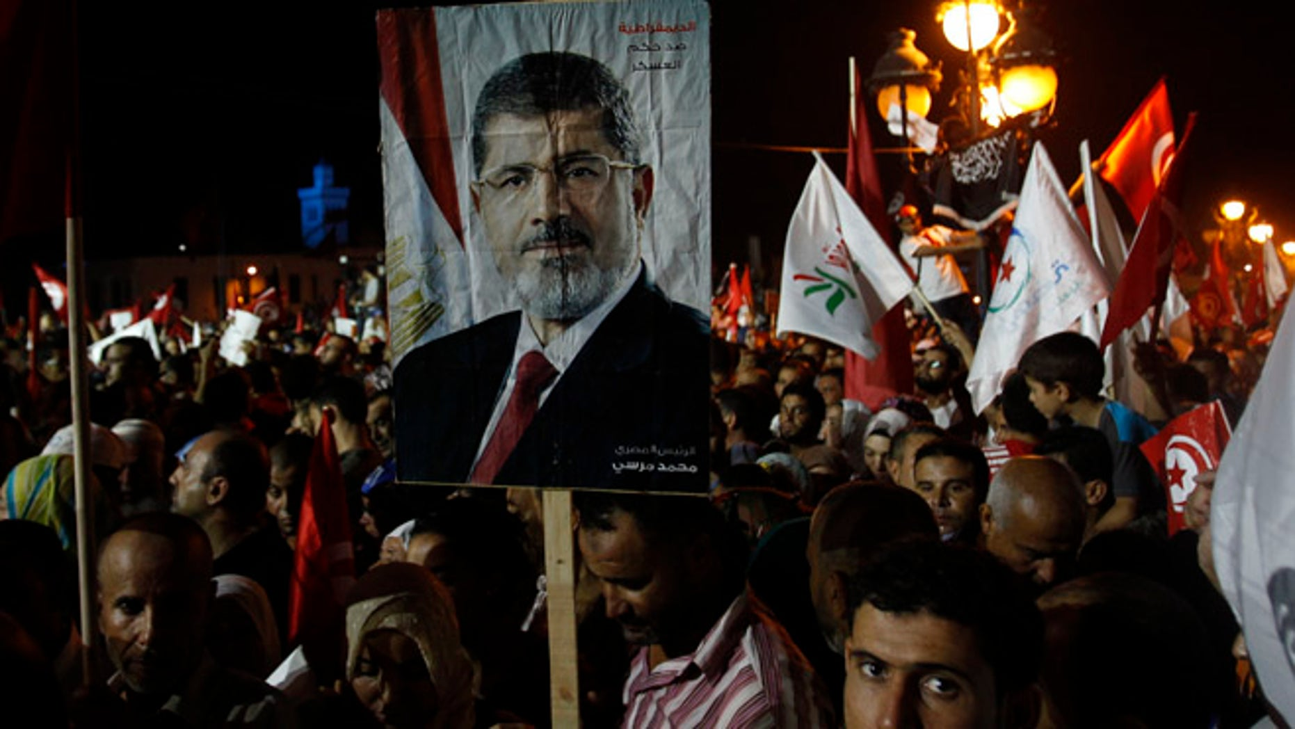 Aug 3, 2013: Supporters of the Islamist Ennahda movement hold a portrait of ousted Egyptian President Mohamed Morsi during a demonstration at Kasbah Square in Tunis.