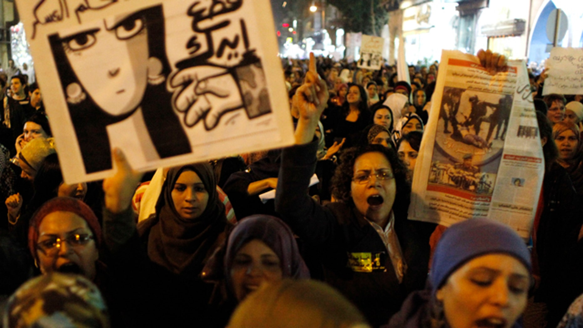 """Dec. 20, 2011: Egyptian women angered by the recent violence used against them in clashes between army soldiers and protesters, one carrying a poster that reads in Arabic """"Down with military rule, Military are liars and We will cut your hand"""" chant anti military slogans during rally that ended in Tahrir Square, Cairo, Egypt."""