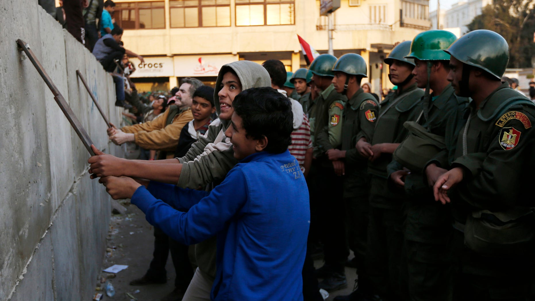 Dec. 9, 2012: Protesters break iron bars on cement blocks, as Egyptian army soldiers stand guard in front of the presidential palace in Cairo, Egypt.