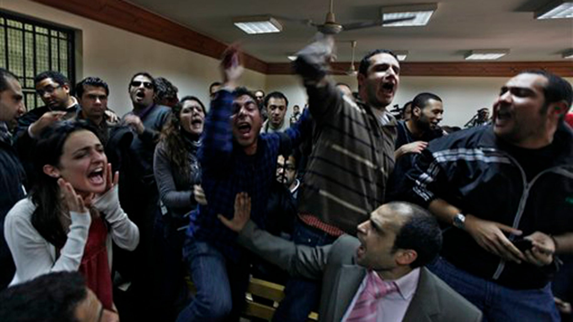 Feb. 26, 2012: Protesters chant anti-military ruling slogans during a trial of employees of pro-democracy groups in Cairo, Egypt.