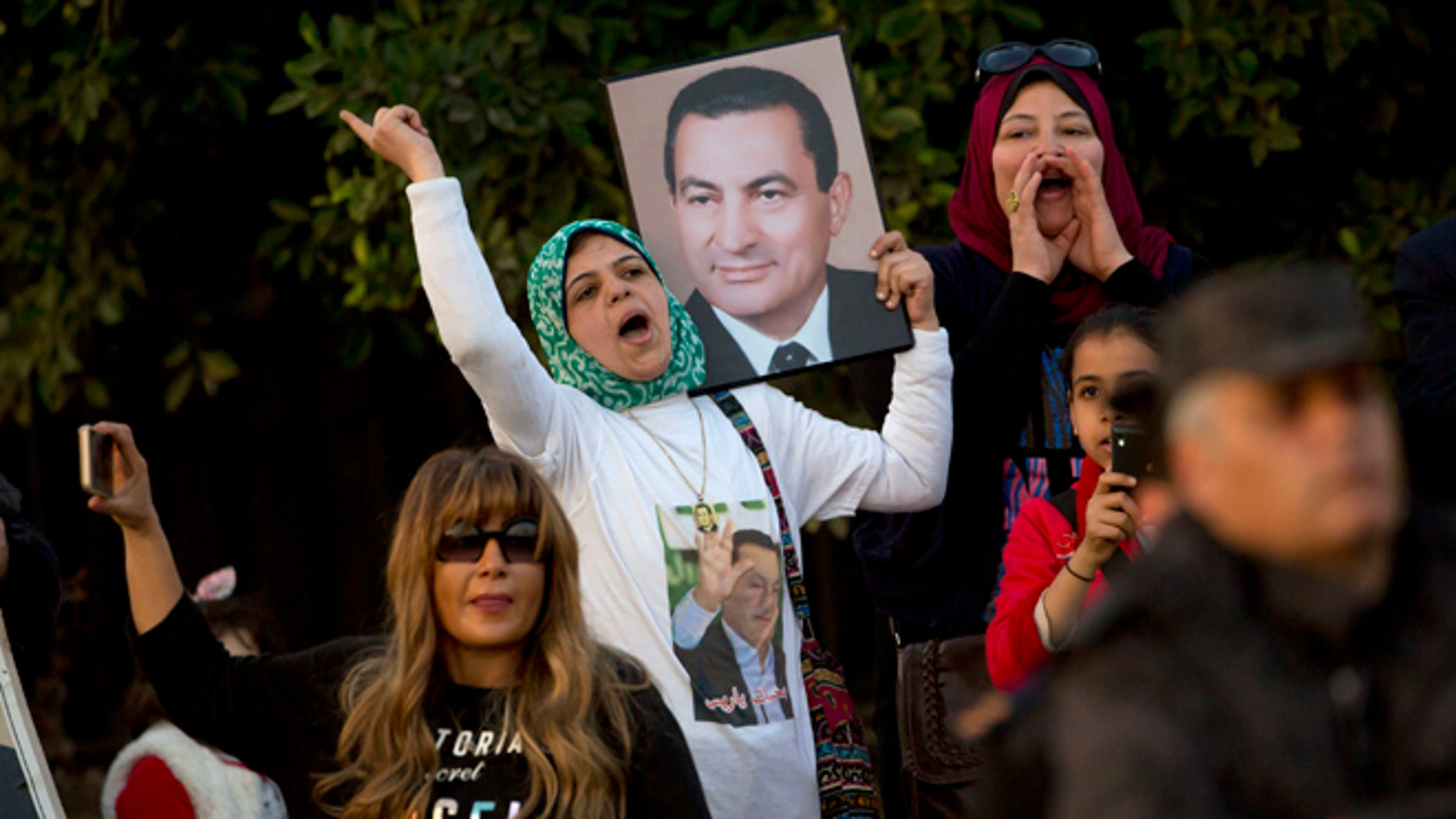 A small number of supporters of ousted former Egyptian President Hosni Mubarak hold posters with his photo, as they celebrate outside Maadi Military Hospital, where he is hospitalized, in Cairo, Egypt, Thursday, March 2, 2017.