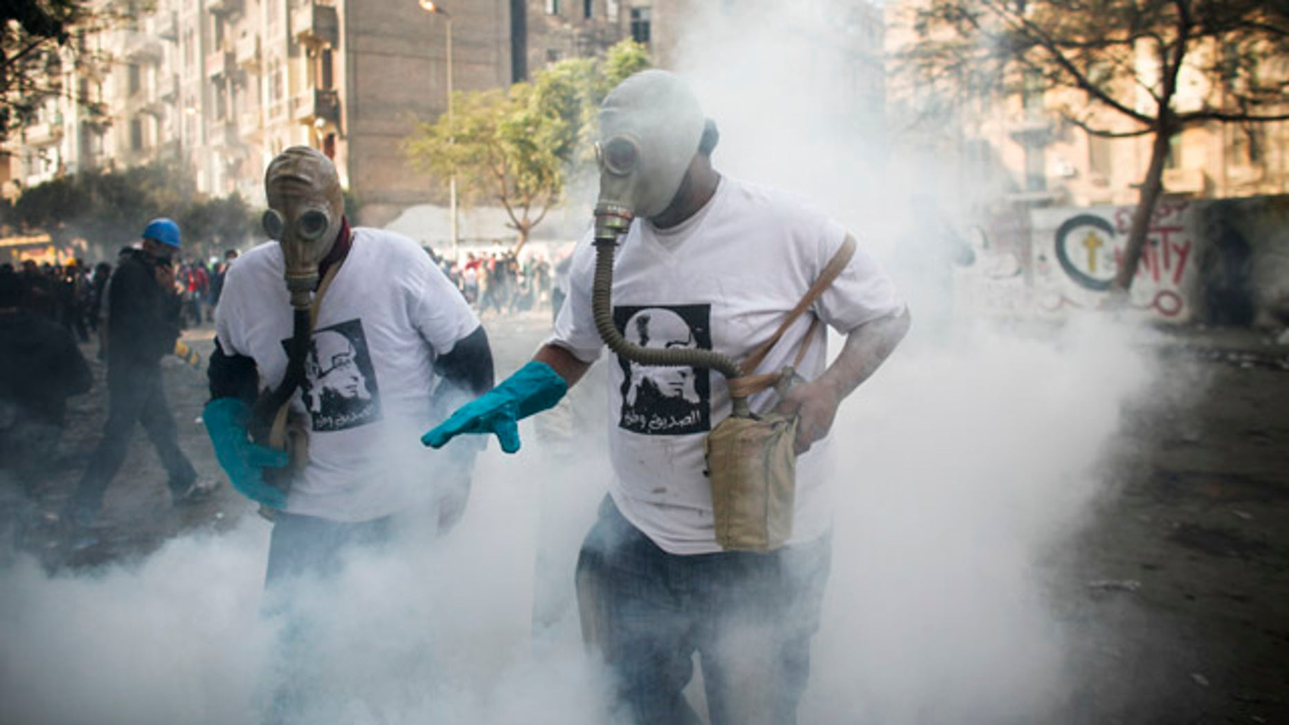 Nov. 23. 2011: Protesters attempt to get rid of a tear gas canister during clashes with Egyptian riot police, not pictured, near Tahrir square in Cairo, Egypt.