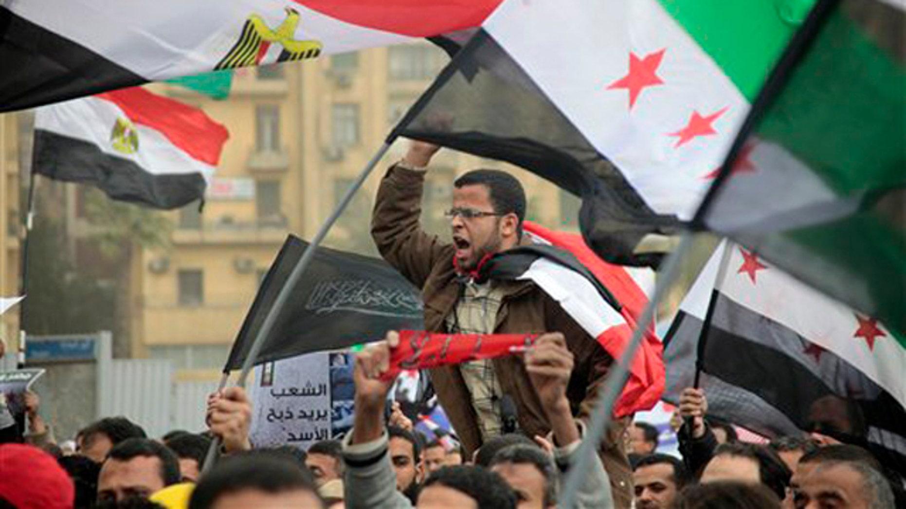 Feb. 17, 2012: Syrian and Egyptian protesters shout slogans during a demonstration against Syrian President Bashar al-Assad in front of the Syrian embassy in Cairo, Egypt.