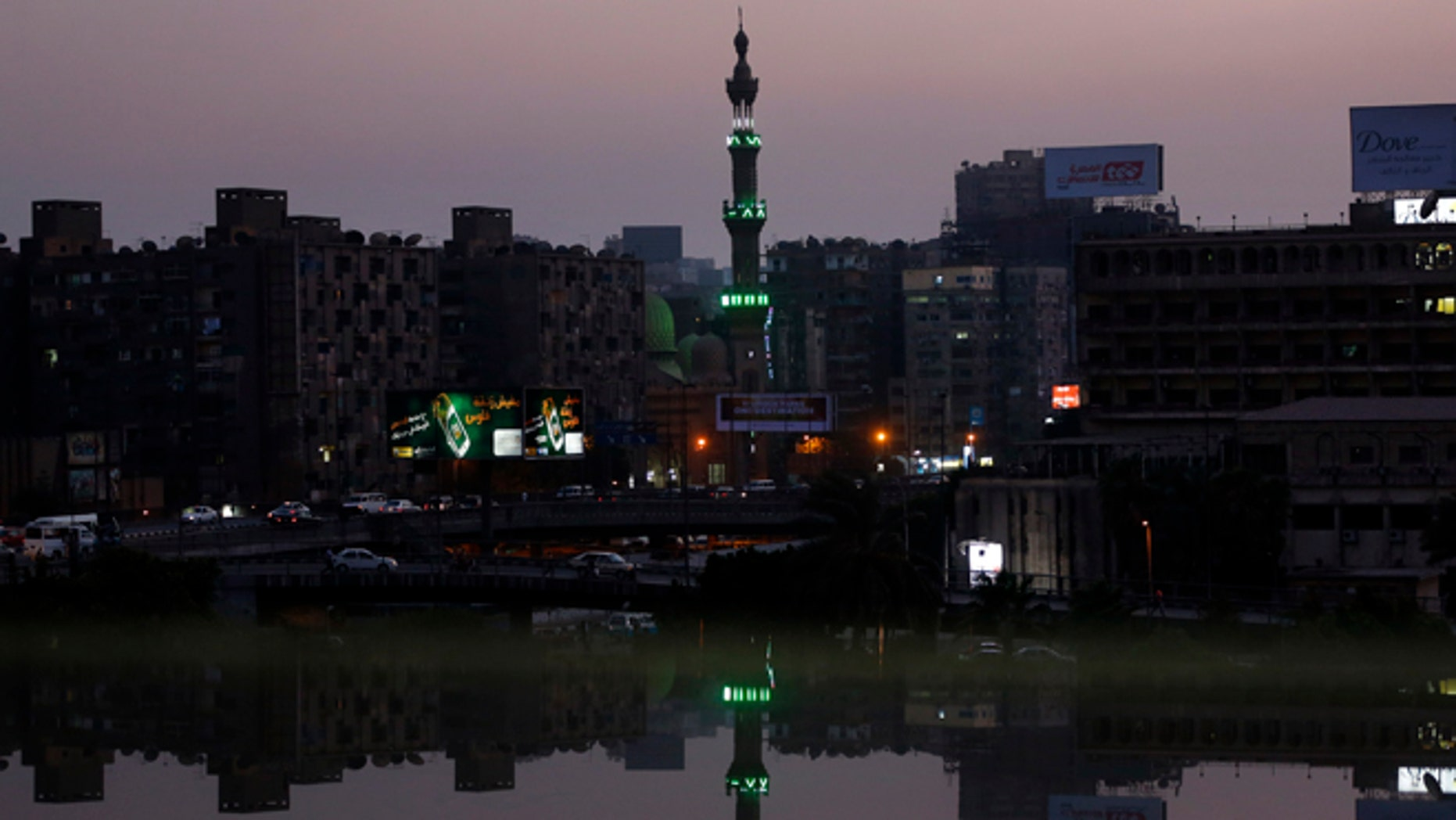 Aug. 25, 2013: A mosque's minaret near the river Nile river is reflected on an open office window in Cairo, Egypt. (AP/Lefteris Pitarakis)