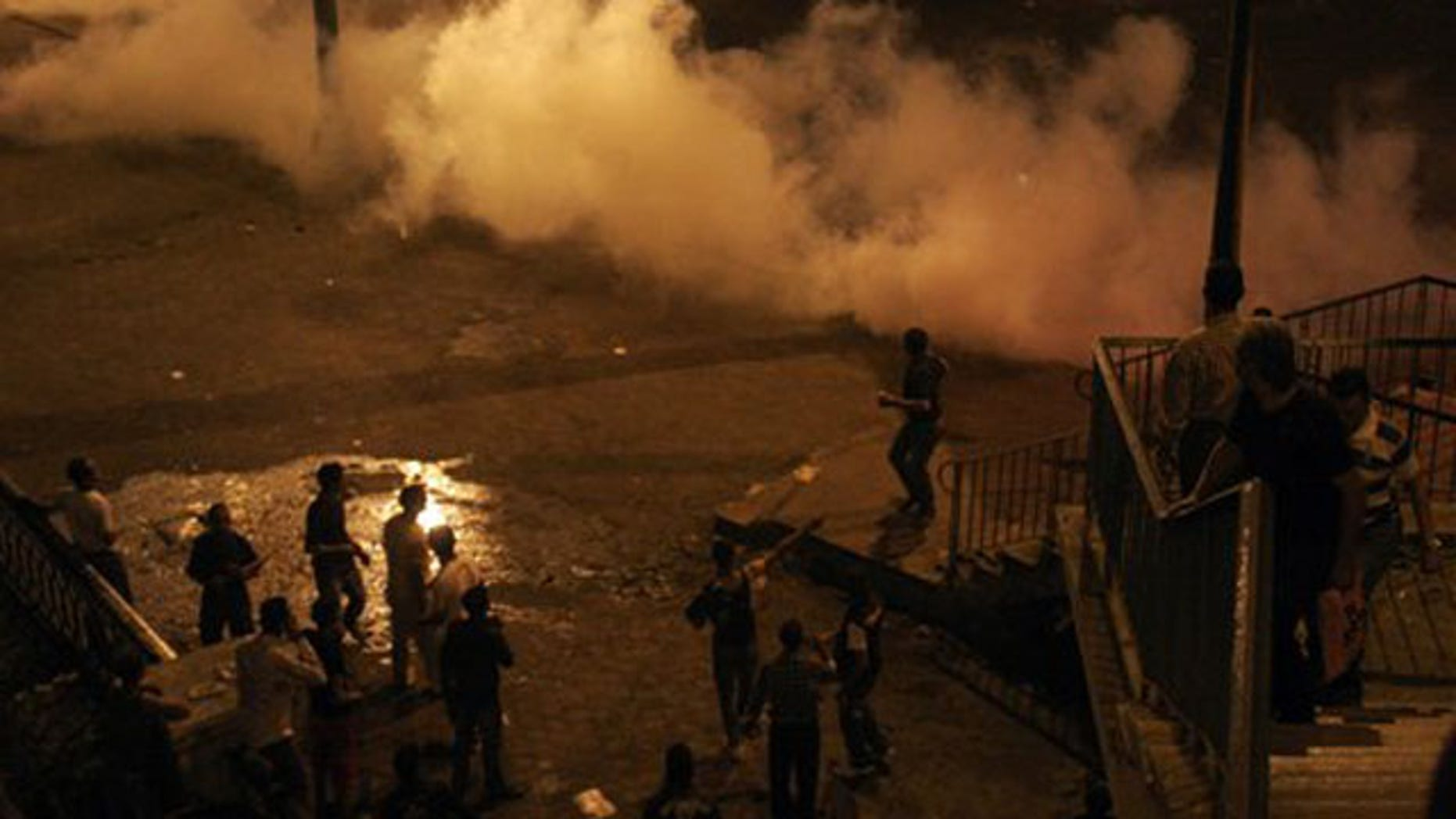 Smoke from tear gas fills the street as protesters clash with Egyptian security forces in Cairo Egypt, Sunday, Oct. 9, 2011.