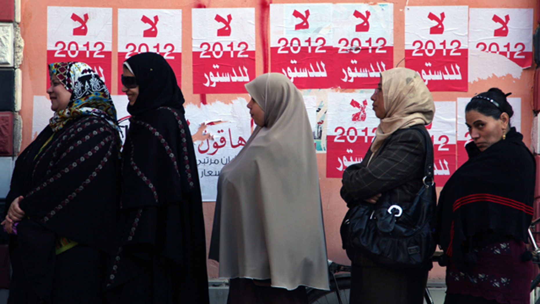 Dec. 22, 2012: Egyptian women line up outside a polling station next to stickers on a wall in Fayoum, about 62 miles south of Cairo, Egypt.
