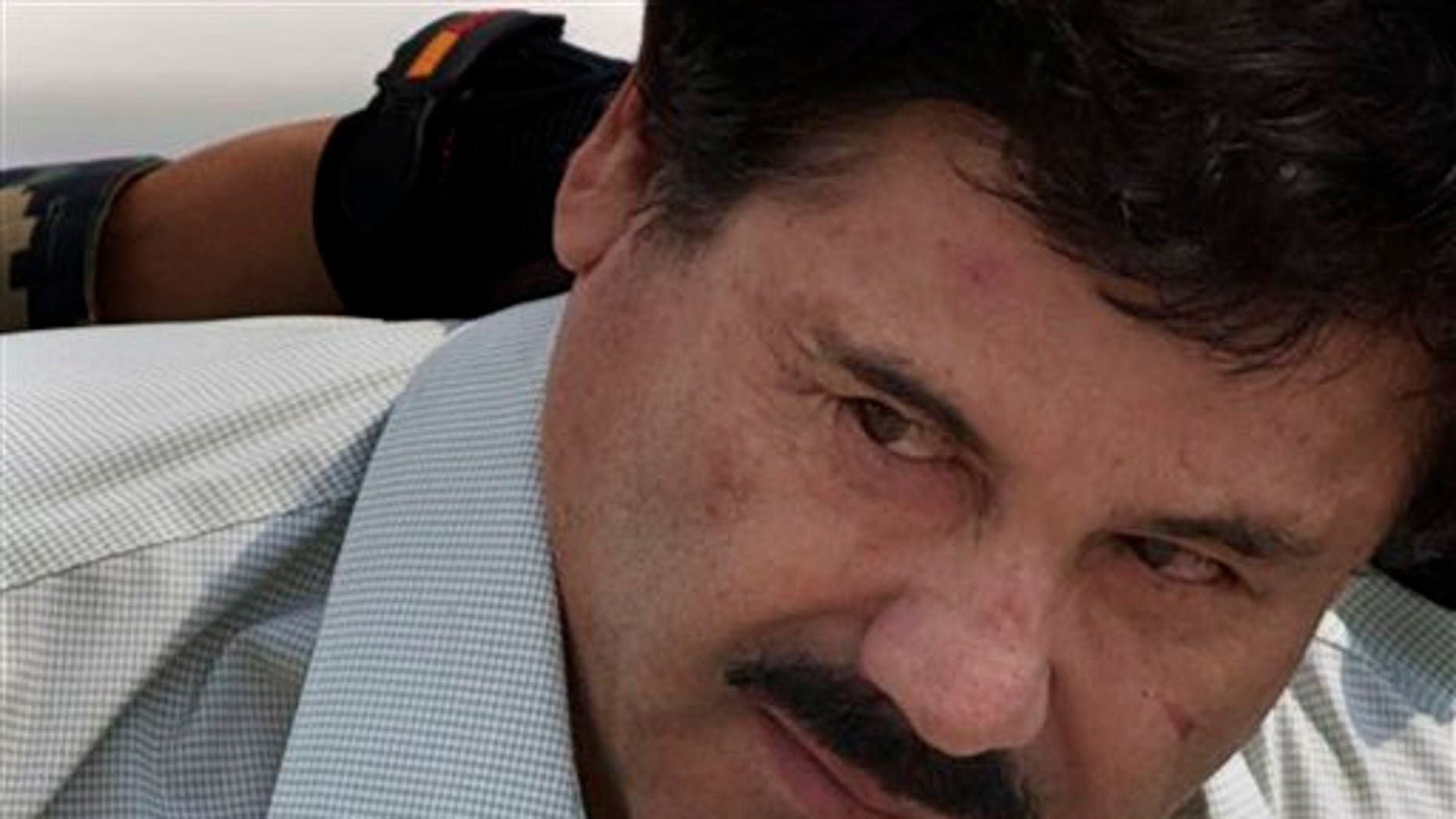 """En esta imagen del 22 de febrero de 2014, Joaquín """"El Chapo"""" Guzmàn es escoltado hacia un helicóptero por miembros de la Marina de México en un hangar del aeropuerto de la Ciudad de México. El comisionado de seguridad nacional de México dijo que el capo podría ser extraditado a Estados Unidos a inicios del año entrante. Renato Sales le dijo a Televisa que podría suceder en enero o febrero. Un abogado de Guzmán dijo recientemente que la corte podría decidir sobre la extradición a finales del año, pero cualquiera de las partes tendría derecho a apelar. (AP Foto/Eduardo Verdugo, Archivo)"""