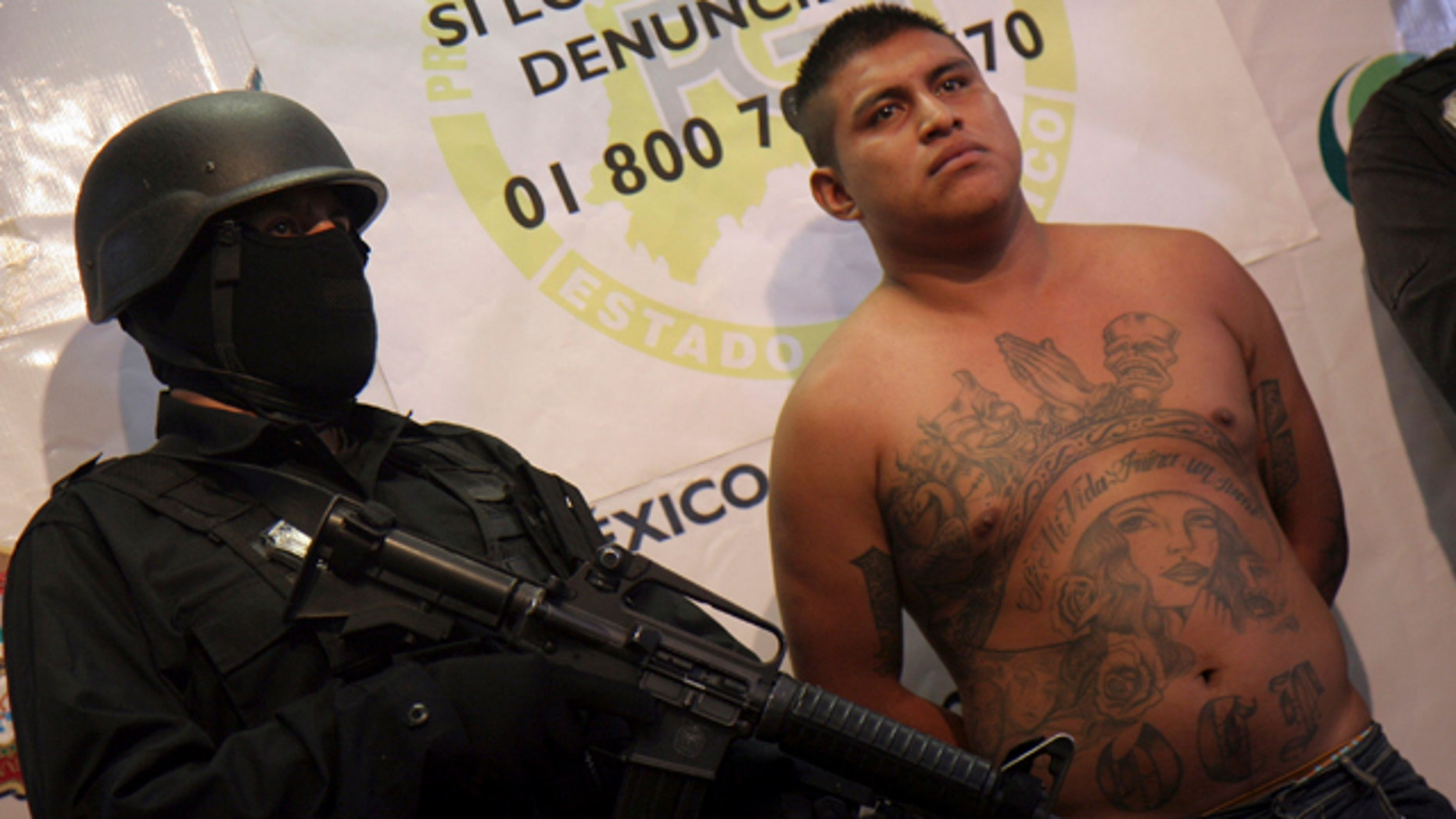 Feb. 17, 2011: A Mexico state policeman stands next to Juan Carlos Vasconcelos, 24, during a presentation to the press in Toluca, Mexico.