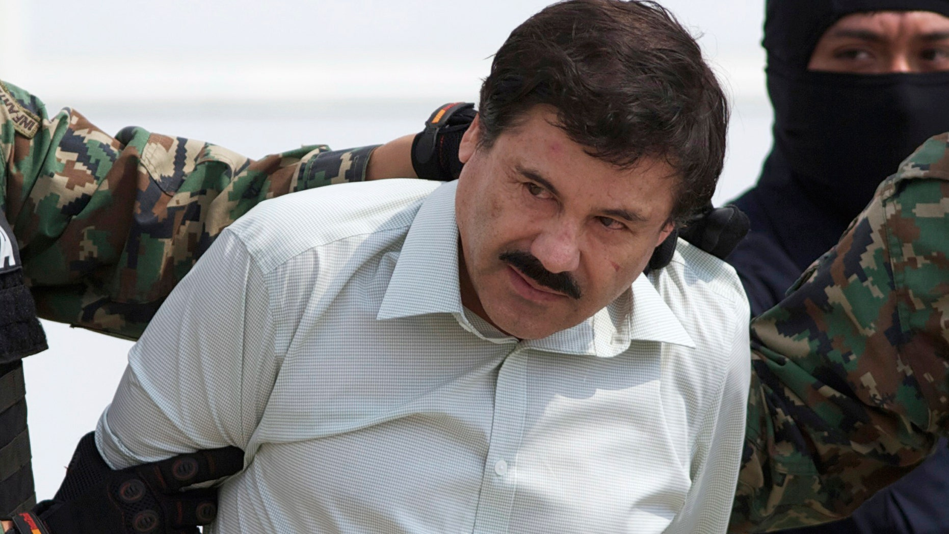 """Feb. 22, 2014:  Joaquin """"El Chapo"""" Guzman, the head of Mexico's Sinaloa Cartel, is escorted to a helicopter in Mexico City following his capture overnight in the beach resort town of Mazatlan."""
