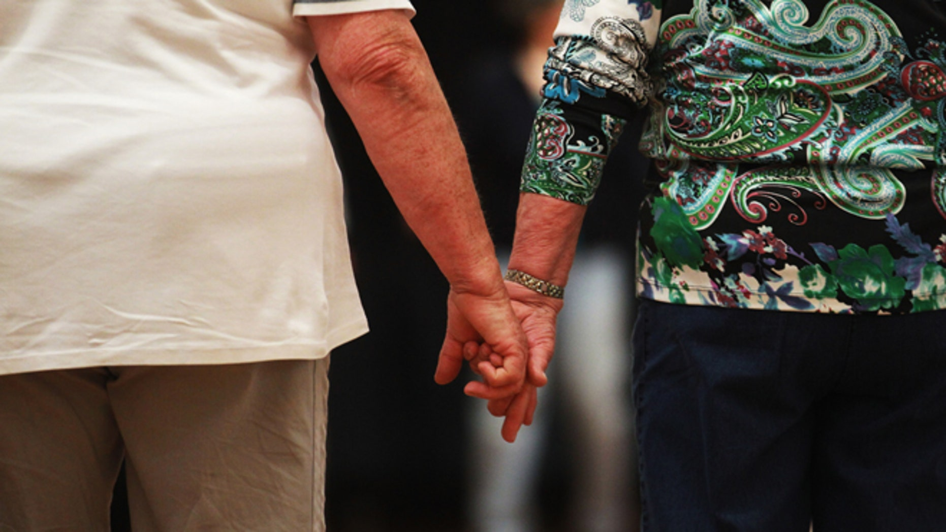 """HAMBURG, GERMANY - MAY 03:  An elderly couple hold hands at a trade fair at the """"Seniorentag 2012"""" senior citizens convention on May 3, 2012 in Hamburg, Germany. The three-day long convention caters specifically to the needs of elderly people, who in Germany, as in the rest of Europe, are becoming an increasingly higher portion of the overall population. Europe as a whole, through its low birth rates and improving health care, is undergoing a demographic shift that has far-reaching consequences for labor markets, public policy planning and government budgets.  (Photo by Joern Pollex/Getty Images)"""
