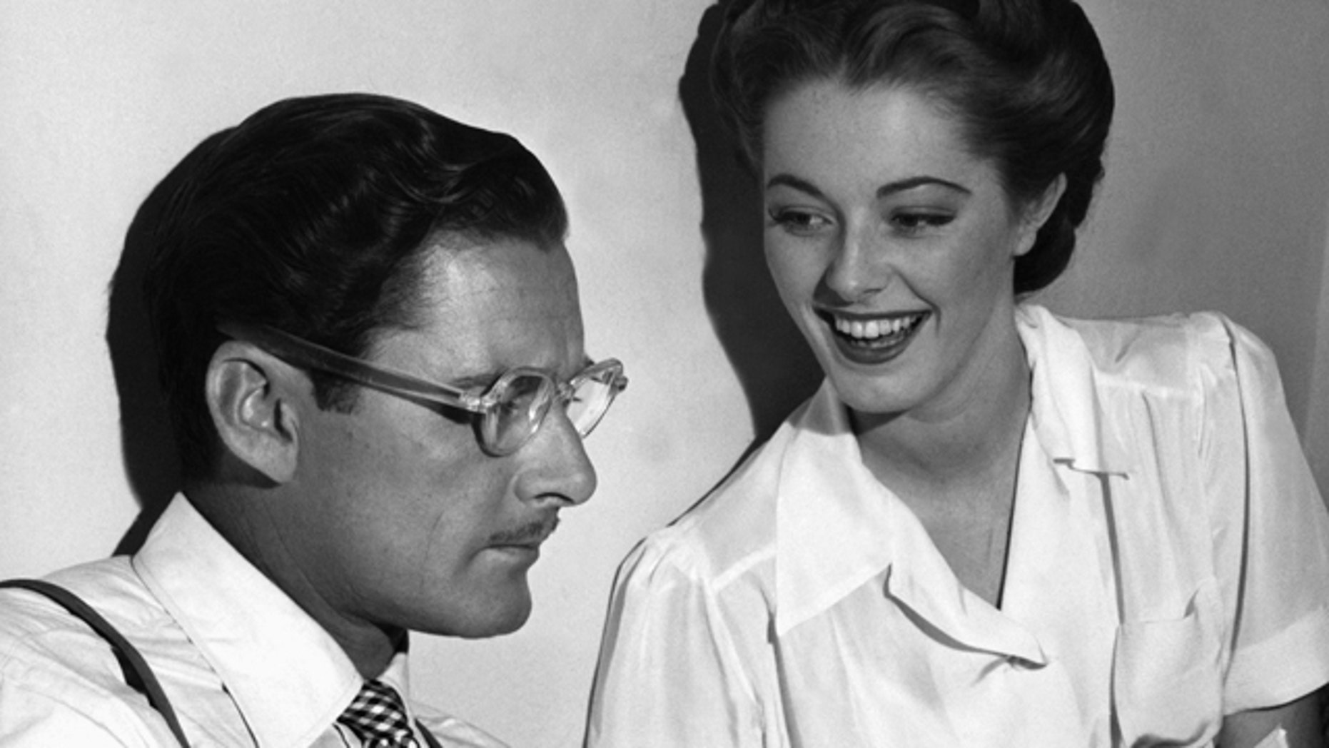 """Errol Flynn seems to be in a literary mood as, between takes on the set of """"Never Say Goodbye,"""" he reads an amusing passage from a new novel to his leading lady, Eleanor Parker, who appears to enjoy the presentation in Los Angeles."""