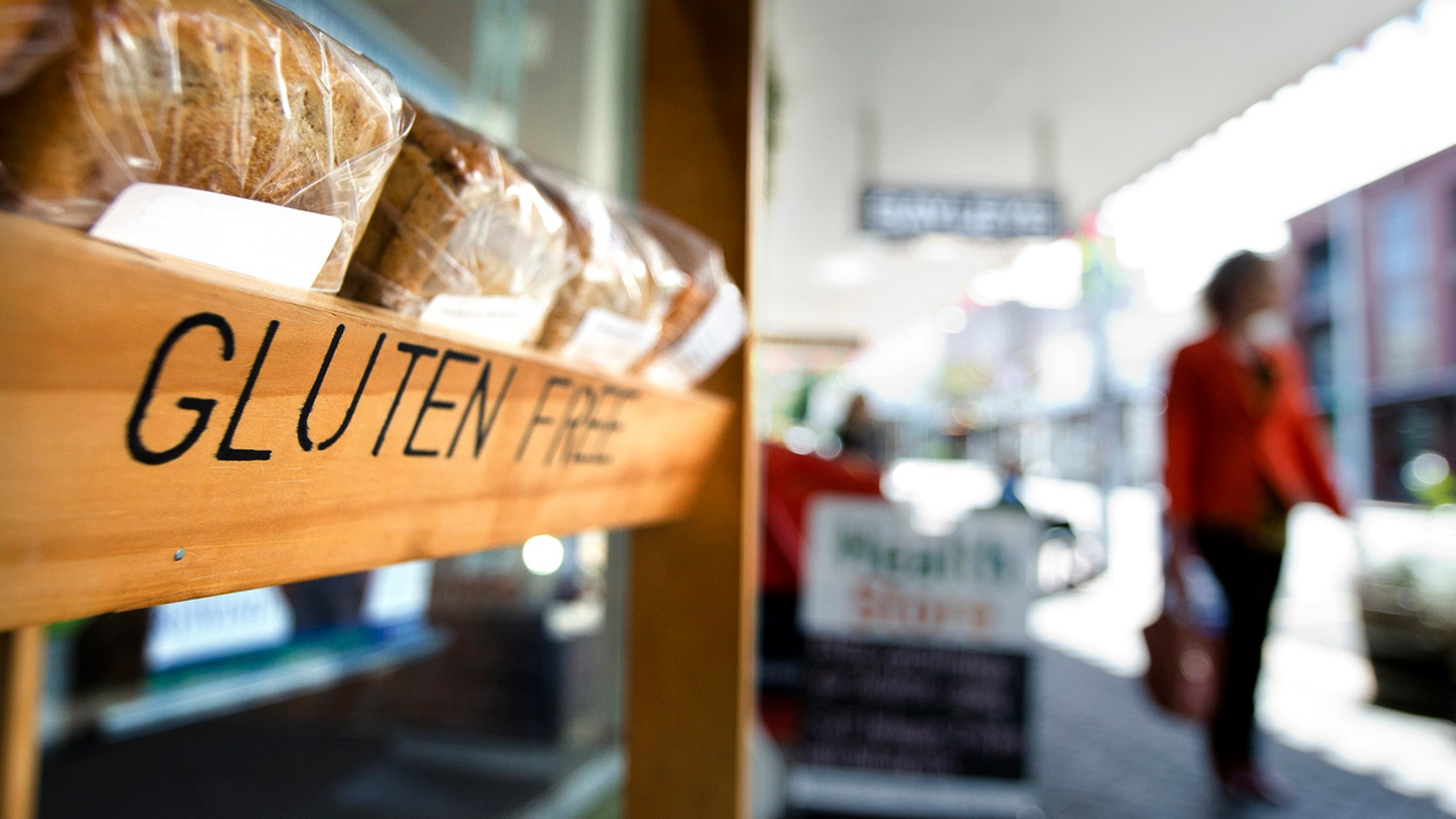 Auckland, New Zealand - October 09, 2013: Woman pass by a Gluten free grocer shop on October 09, 2013. Gluten-free food is normally seen as a diet for celiac disease, nearly 1 out of every 133 people has celiac disease.