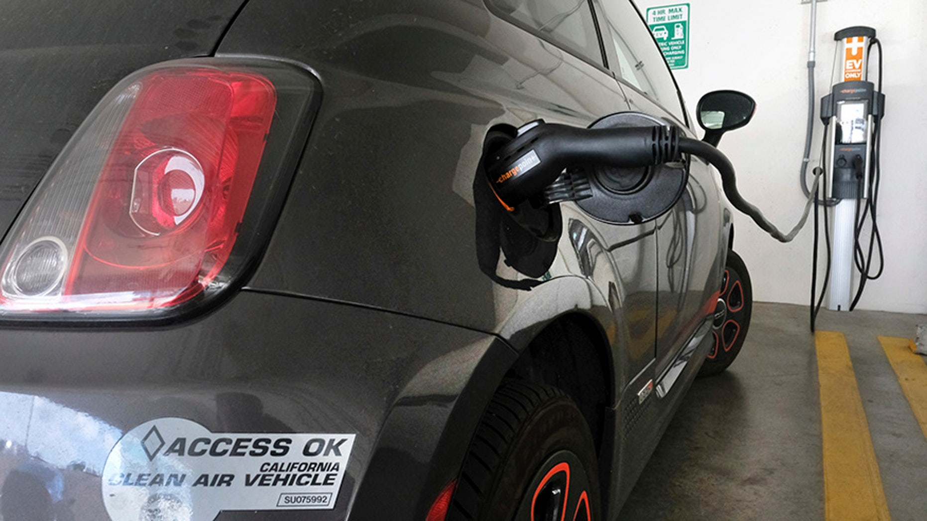 This April 25, 2016, photo shows an electric Fiat plugged into a charging station in a parking lot in Los Angeles. California could spend up to $3 billion under a bill that would widely expand its consumer rebate program for zero-emission vehicles. The Legislature is pushing forward a bill that could lift rebates from $2,500 to $10,000 or more for a compact electric car. Current rebates have done little to boost sales. (AP Photo/Richard Vogel)
