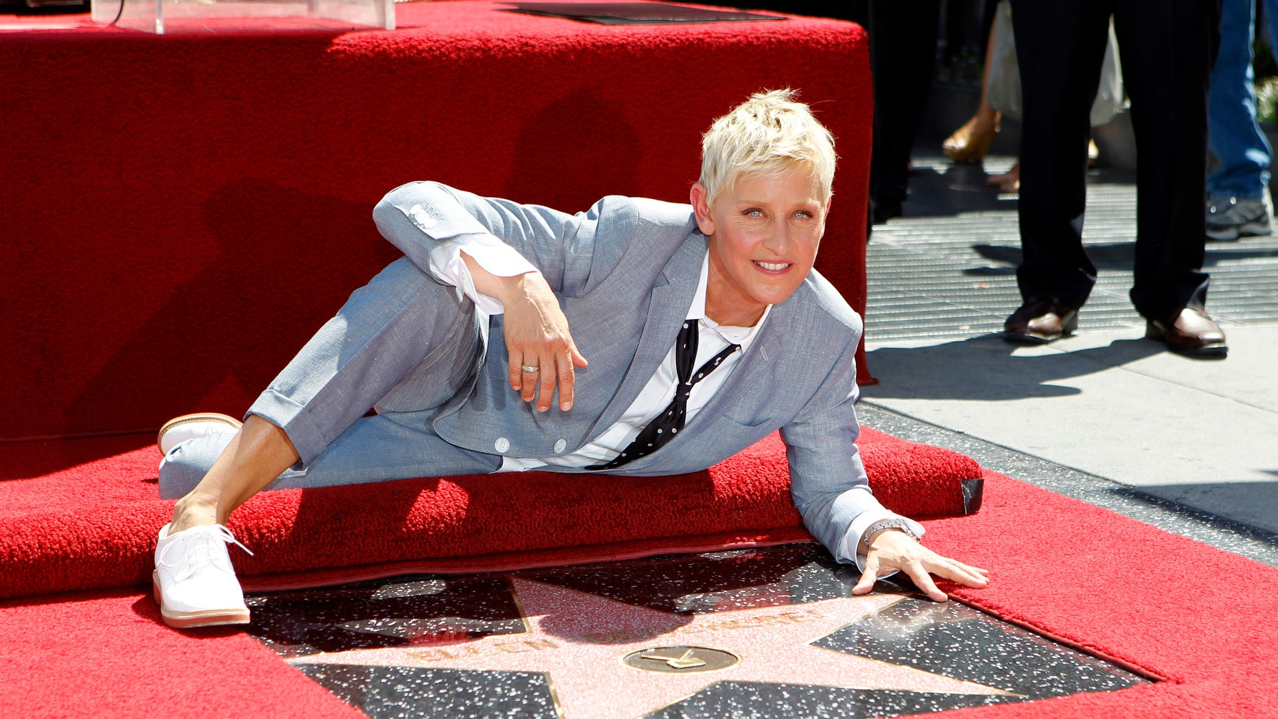 Television personality Ellen DeGeneres poses by her star after it was unveiled on the Walk of Fame in Hollywood, California September 4, 2012. REUTERS/Mario Anzuoni (UNITED STATES - Tags: ENTERTAINMENT) - RTR37HN3