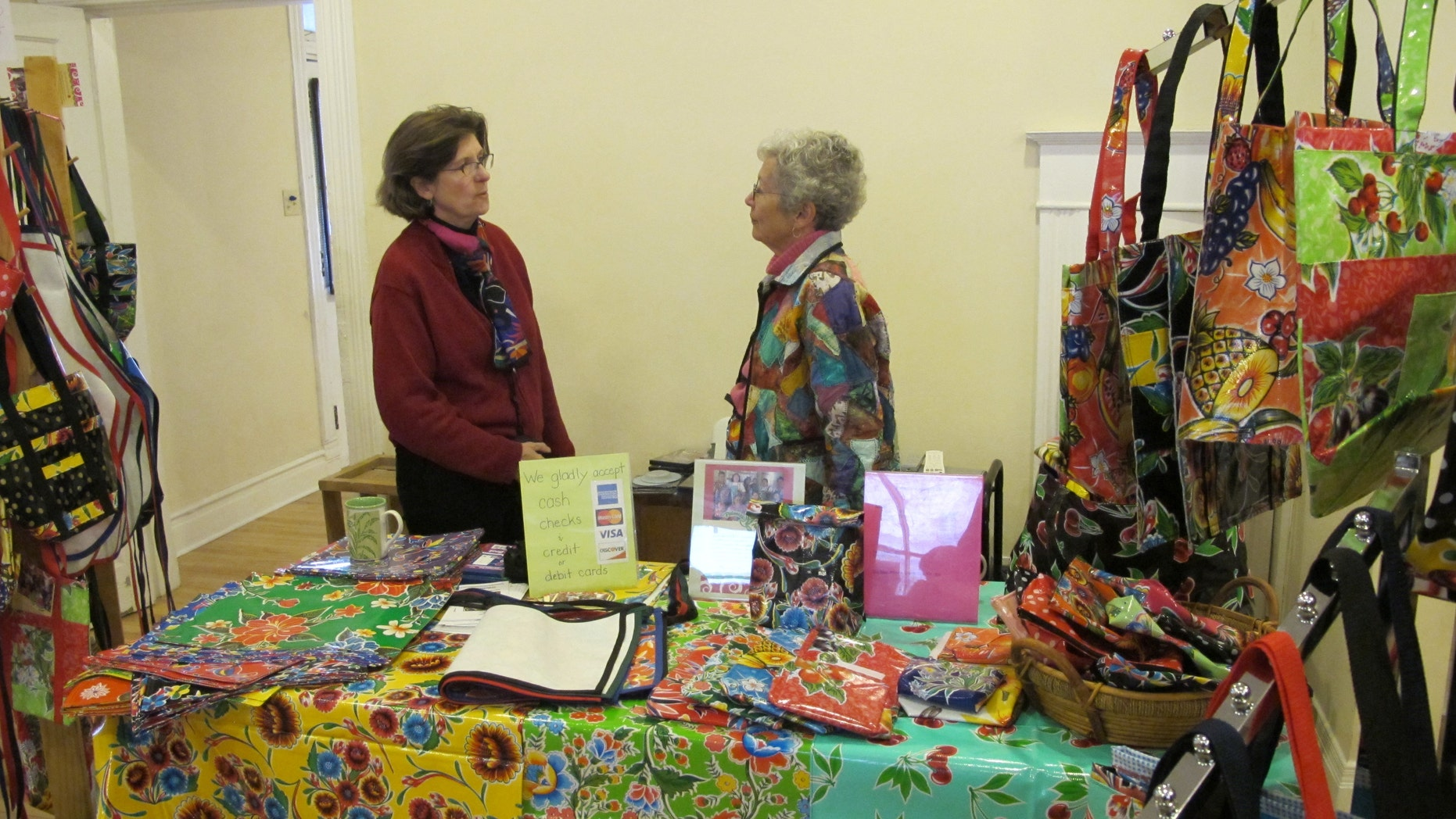 Polly Edmunds from Border Partners speaks with a fellow seller. Edmunds sells waterproof items made from Mexican oilcloth to benefit Palomas Oilcloth Designs.