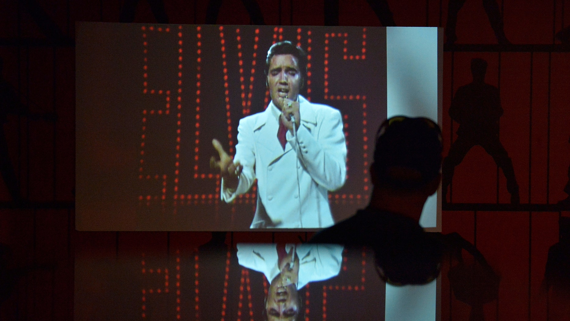 """File photo - A man watches a video of Elvis Presley performing during the grand opening of """"Elvis Presley's Memphis"""", a $45 million, state-of-the-art entertainment and museum complex, in Memphis, Tennessee, U.S., March 2, 2017. (REUTERS/Brandon Dill)"""