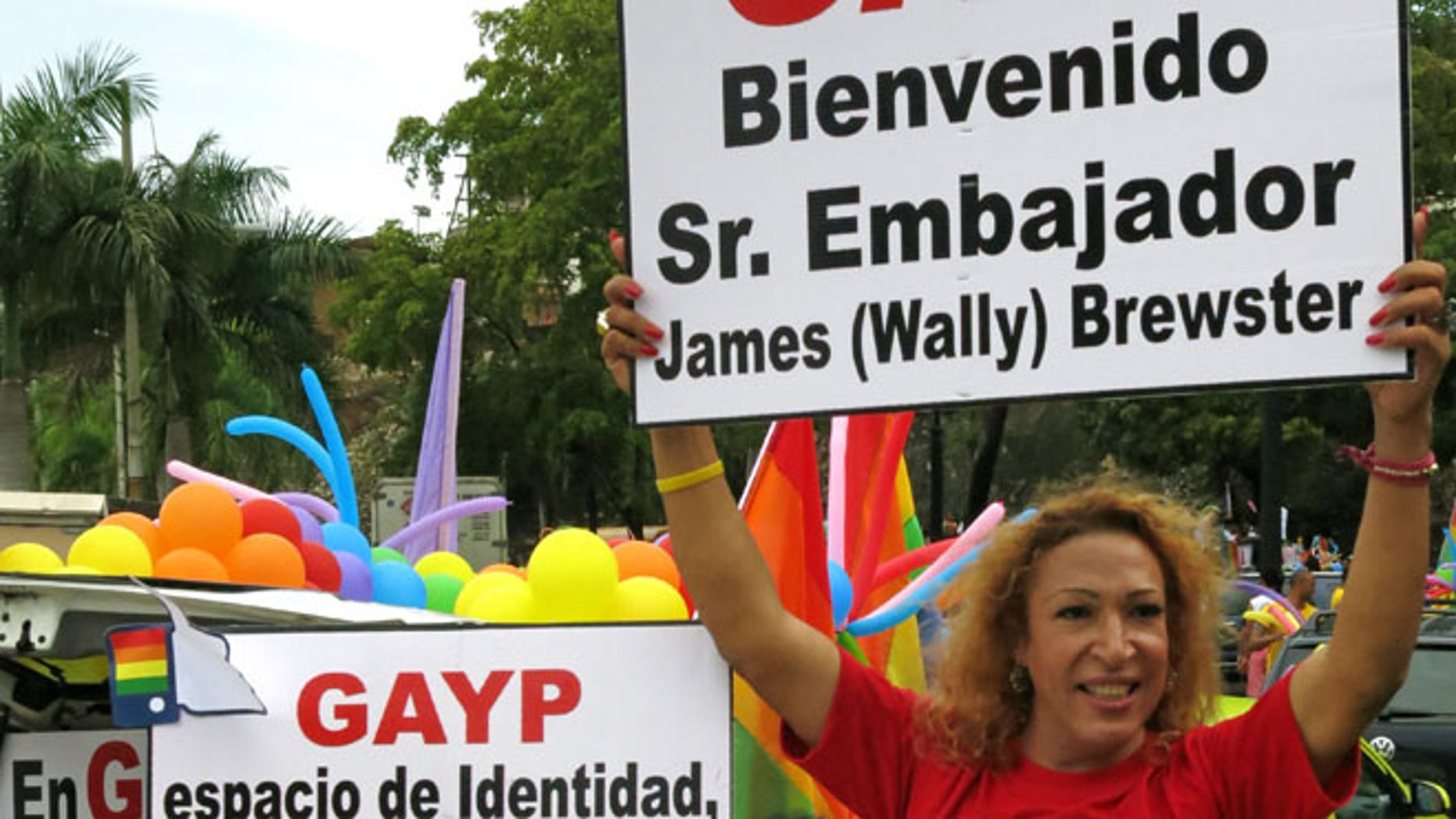"""FILE - In this June 30, 2013 file photo, people welcome U.S. Ambassador James """"Wally"""" Brewster during a gay pride parade in Santo Domingo, Dominican Republic. The signs read in Spanish """"Welcome Mr. Ambassador James """"Wally"""" Brewster,"""" right, and """"Identity space, equality zone."""" Activists say Brewster's presence has helped a cultural shift that has allowed gay Dominicans to run for office openly as homosexuals. âWally has become an iconic figure in the LGBT movement because the movement does have strong local figures,â said prominent activist Alexander Mundary. (AP Photo/Ezequiel Abiu Lopez, File)"""