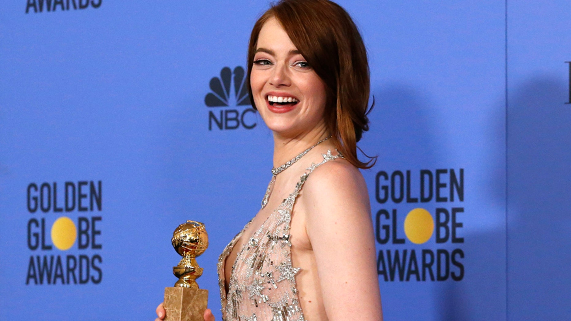 """Emma Stone poses with her award for Best Performance by an Actress in a Motion Picture - Musical or Comedy for her role in """"La La Land"""" during the 74th Annual Golden Globe Awards"""