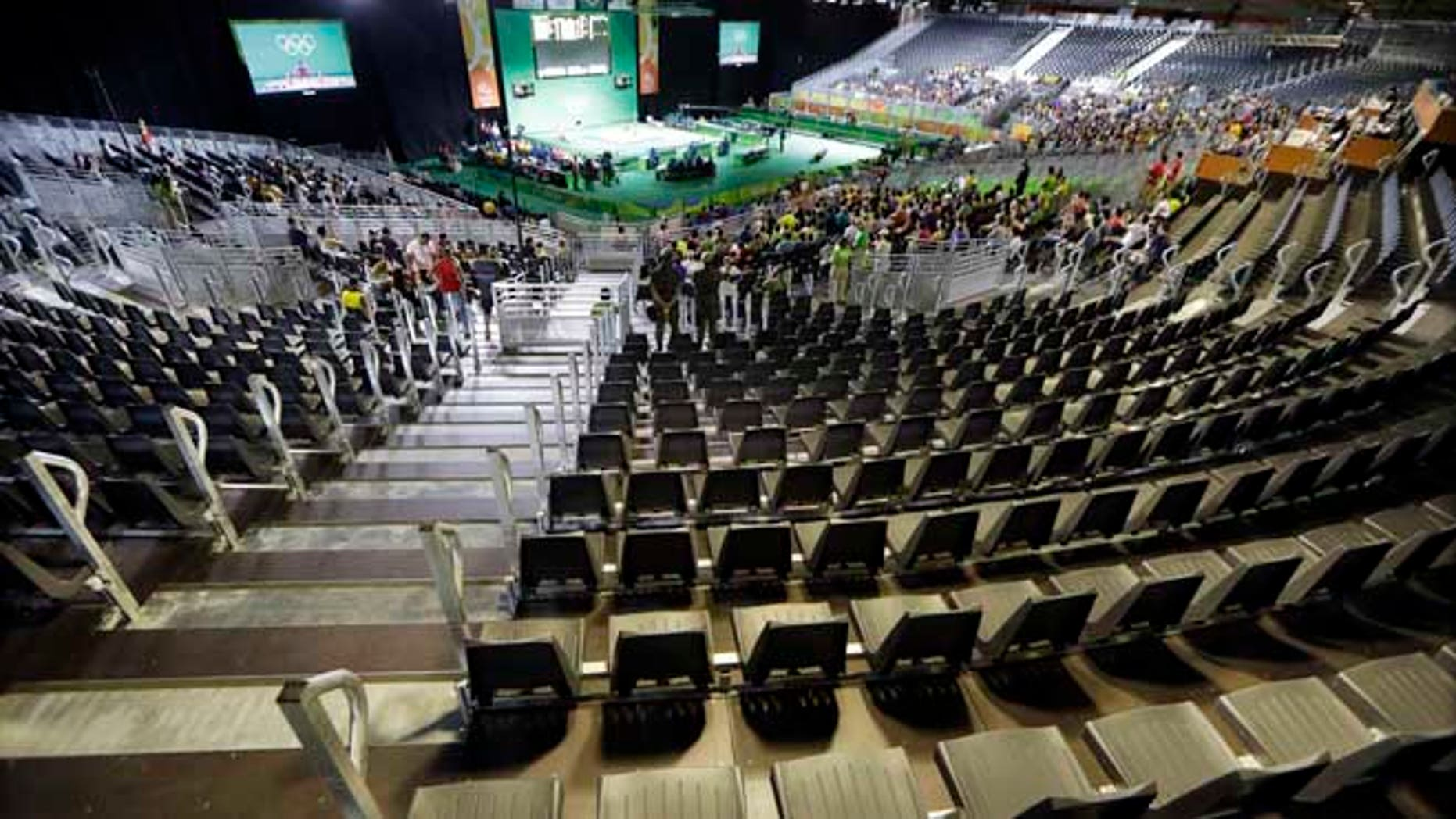 The majority of the spectator seats are empty during the men's 56kg weightlifting competition at the 2016 Summer Olympics in Rio de Janeiro, Brazil, Sunday, Aug. 7, 2016. (AP Photo/Mark Humphrey)