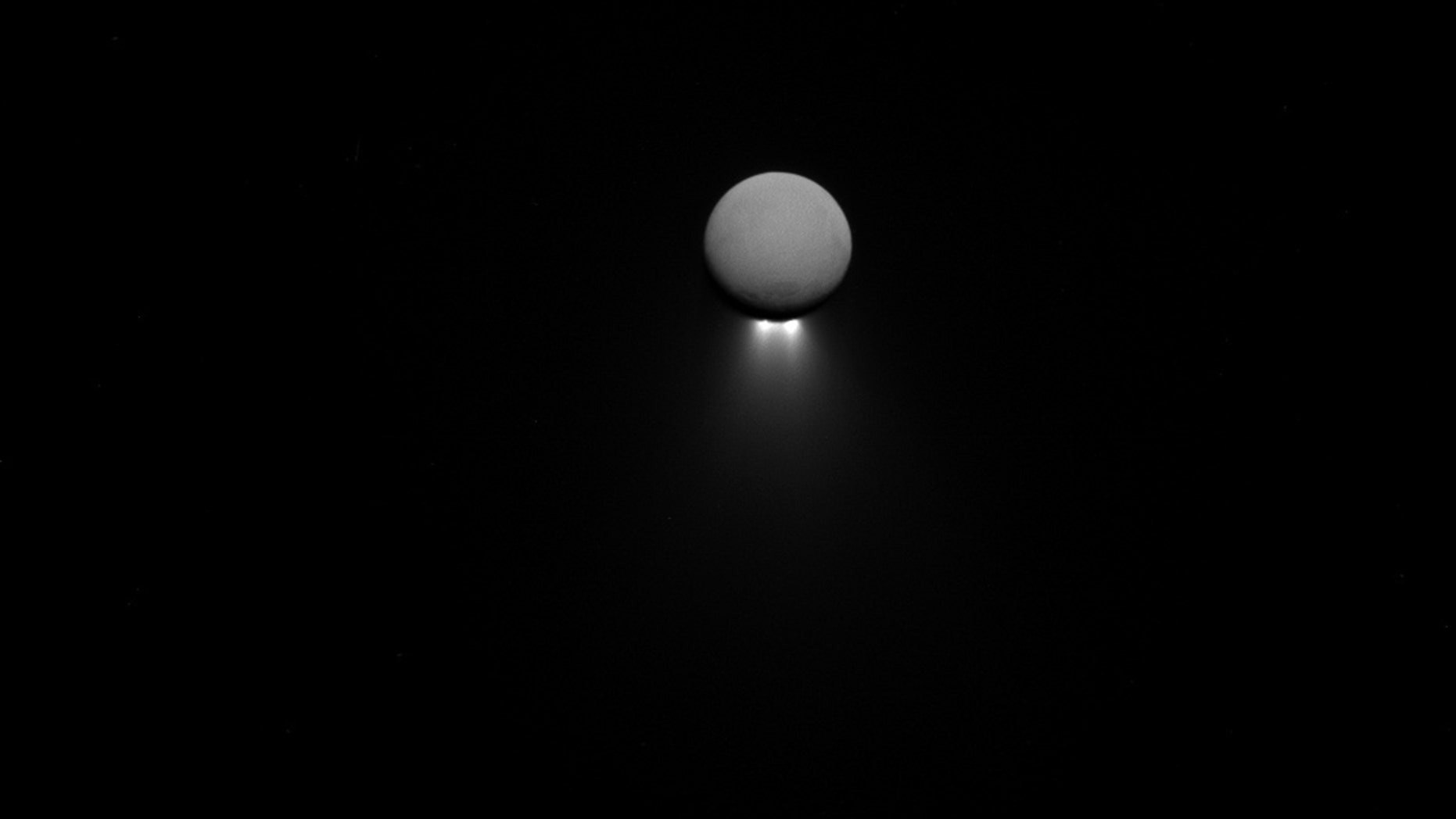 Saturn's moon Enceladus releases jets of water ice as imaged by the Cassini spacecraft in April. The moon shines in reflected Saturn light, while the jets are backlit by the sun.