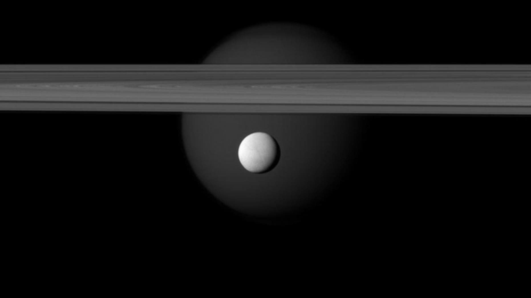 Saturn's icy moon Enceladus hangs below the gas giant's rings while Titan lurks in the background, in this new image taken by the Cassini spacecraft on March 12, 2012.