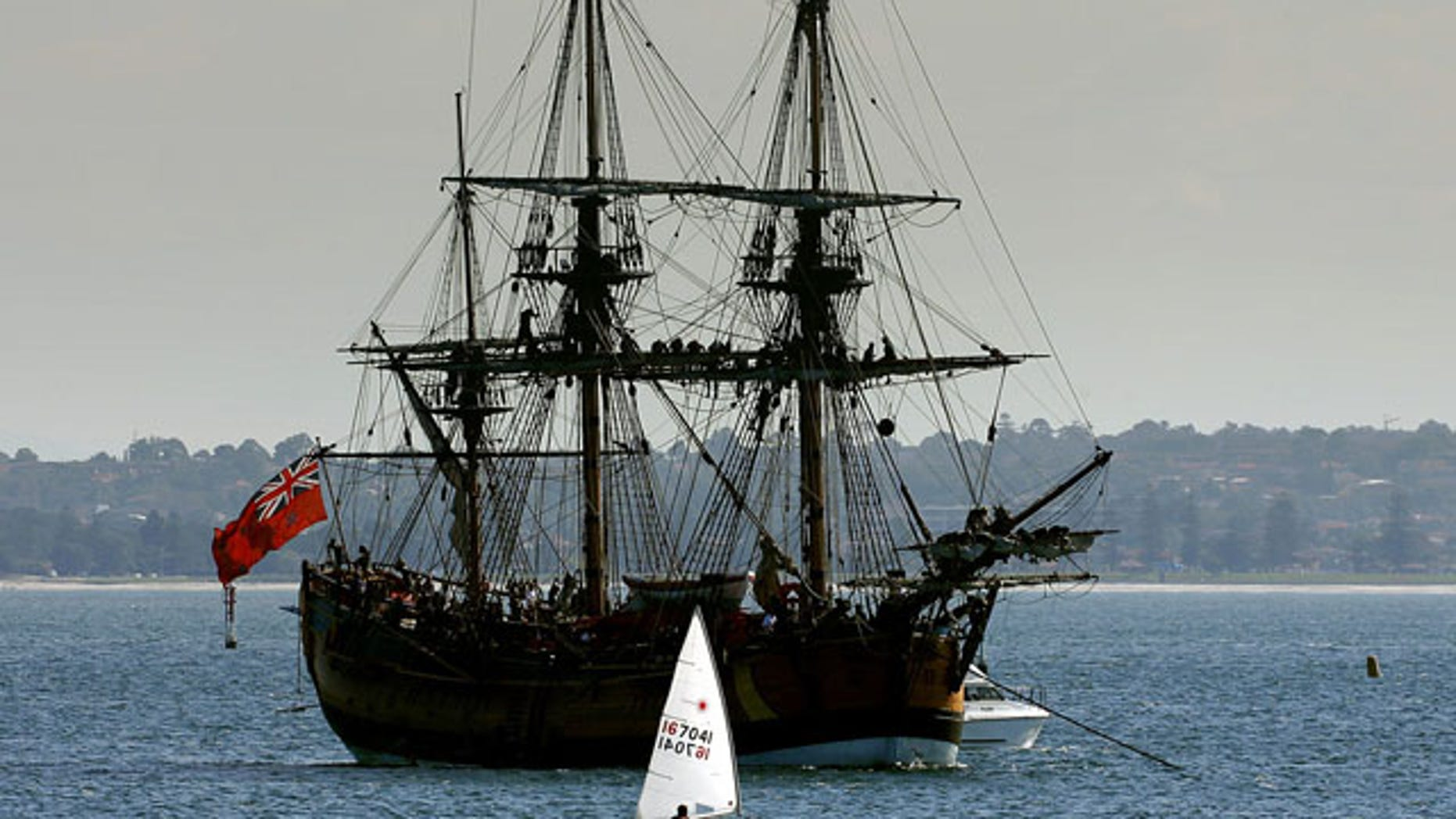 Crew members sit atop the masts of a replica of the famous 18th century ship The Endeavour in Botany Bay.