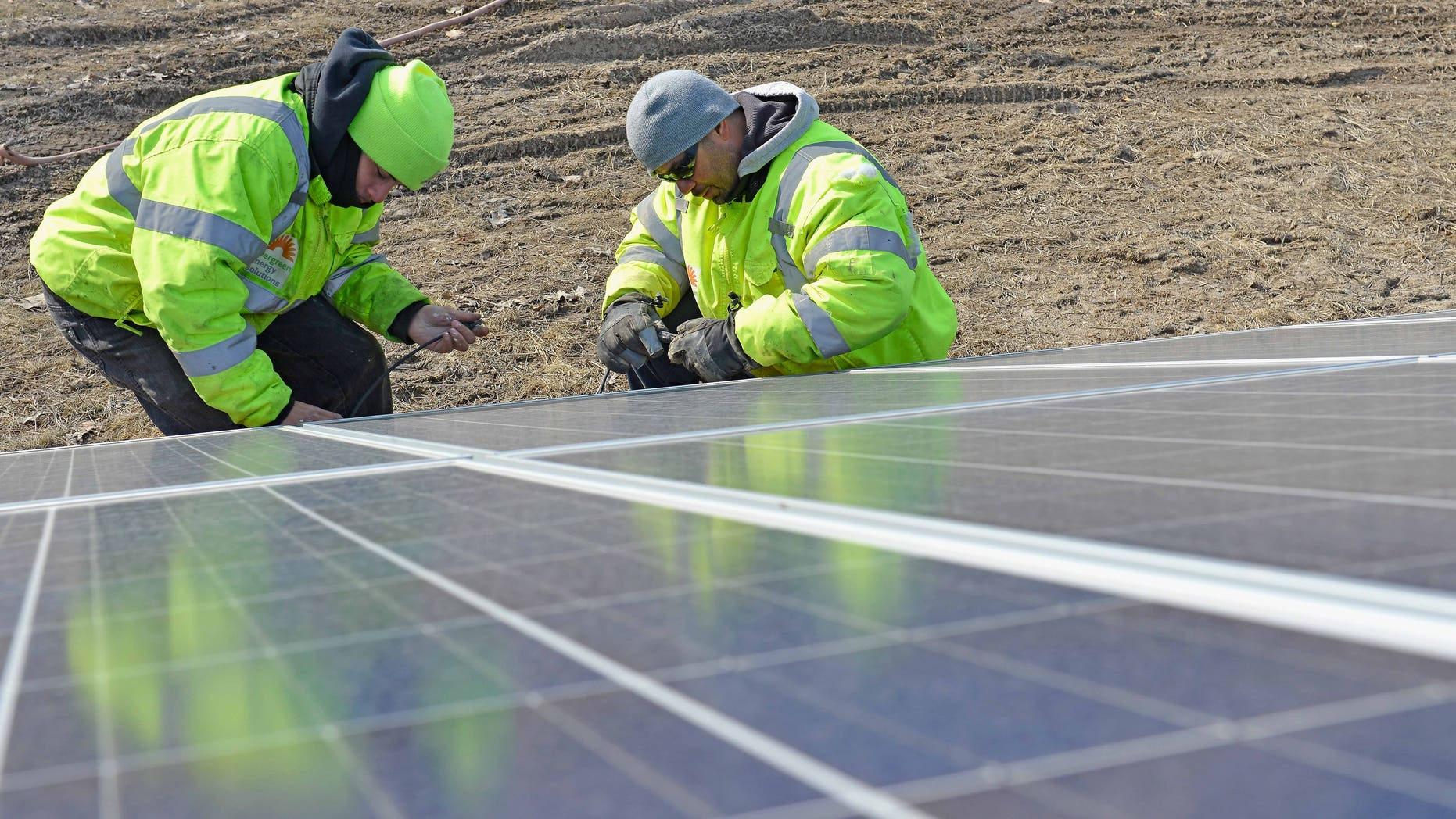 CLEVELAND, OH - MARCH 25:  (L-R) Orlando Santaella Jr. and Orlando Santaella Sr. of Evergreen Energy Solutions work on a ground-mounted solar array located on Euclid Ave across the street from Lakeview Cemetery  on March 25, 2014 in Cleveland, Ohio.  (Photo by Duane Prokop/Getty Images for TakePart.org)