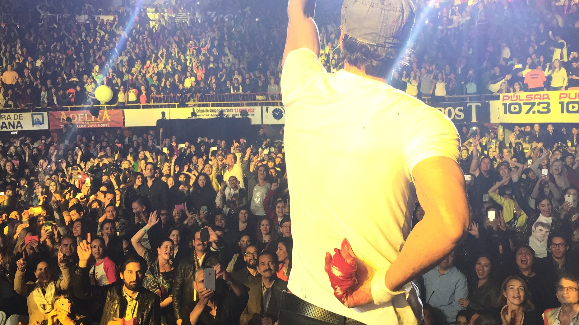May 30, 2015. Enrique Iglesias holds his bloodied hand behind his back during a concert in Tijuana, Mexico.