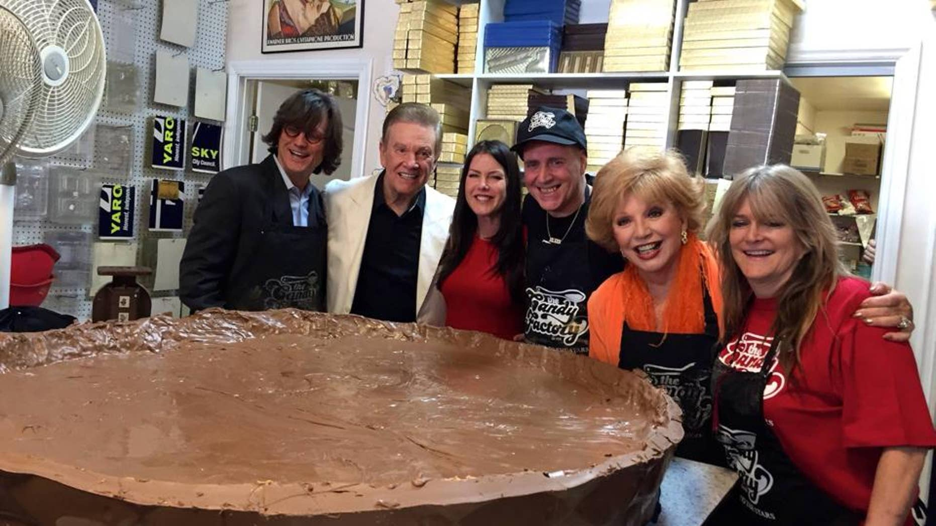 Confectioners and helpers pose with the giant creation.