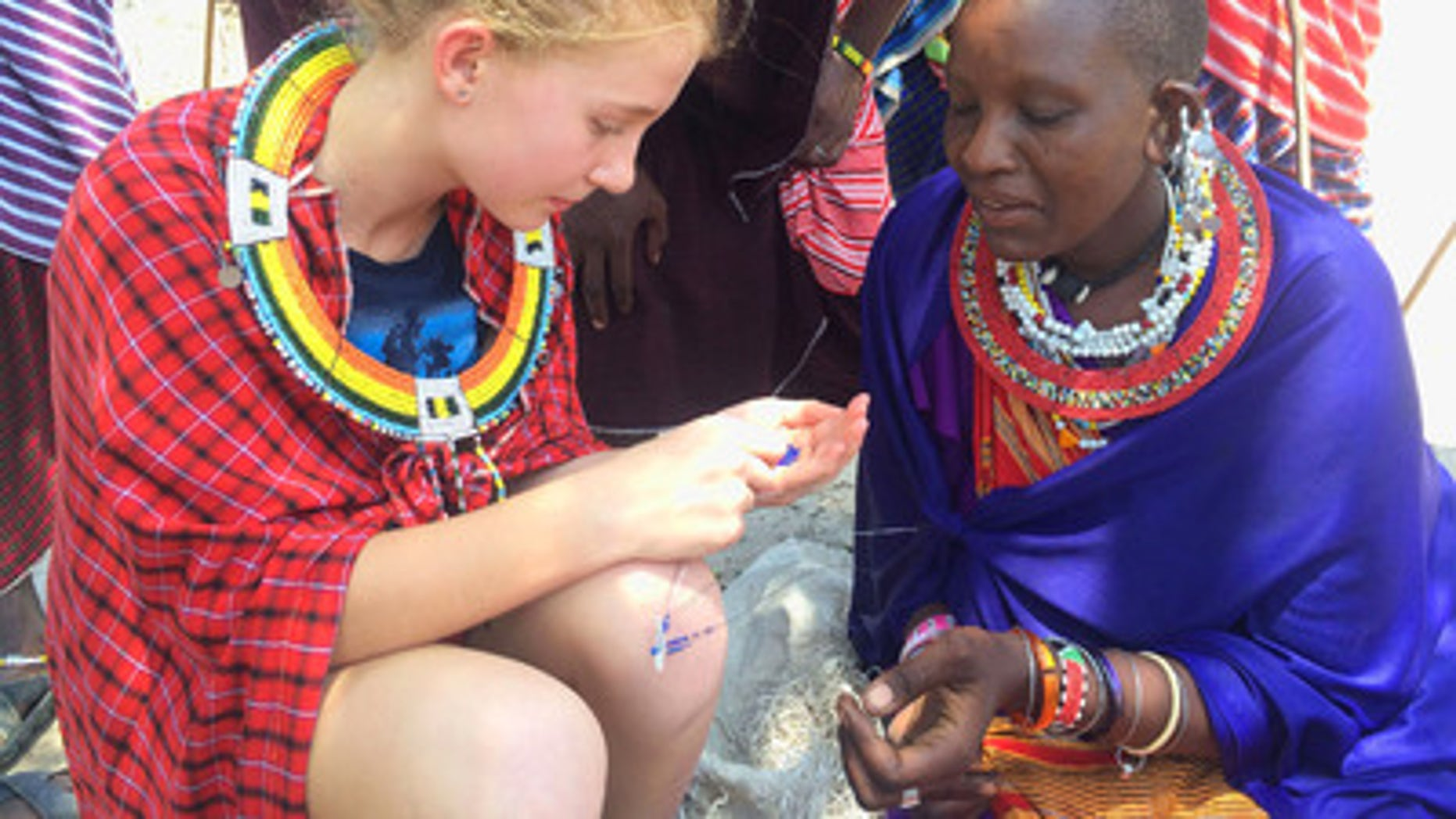 Dolan family spending time with the locals, learning how to make bracelets in Tanzania.