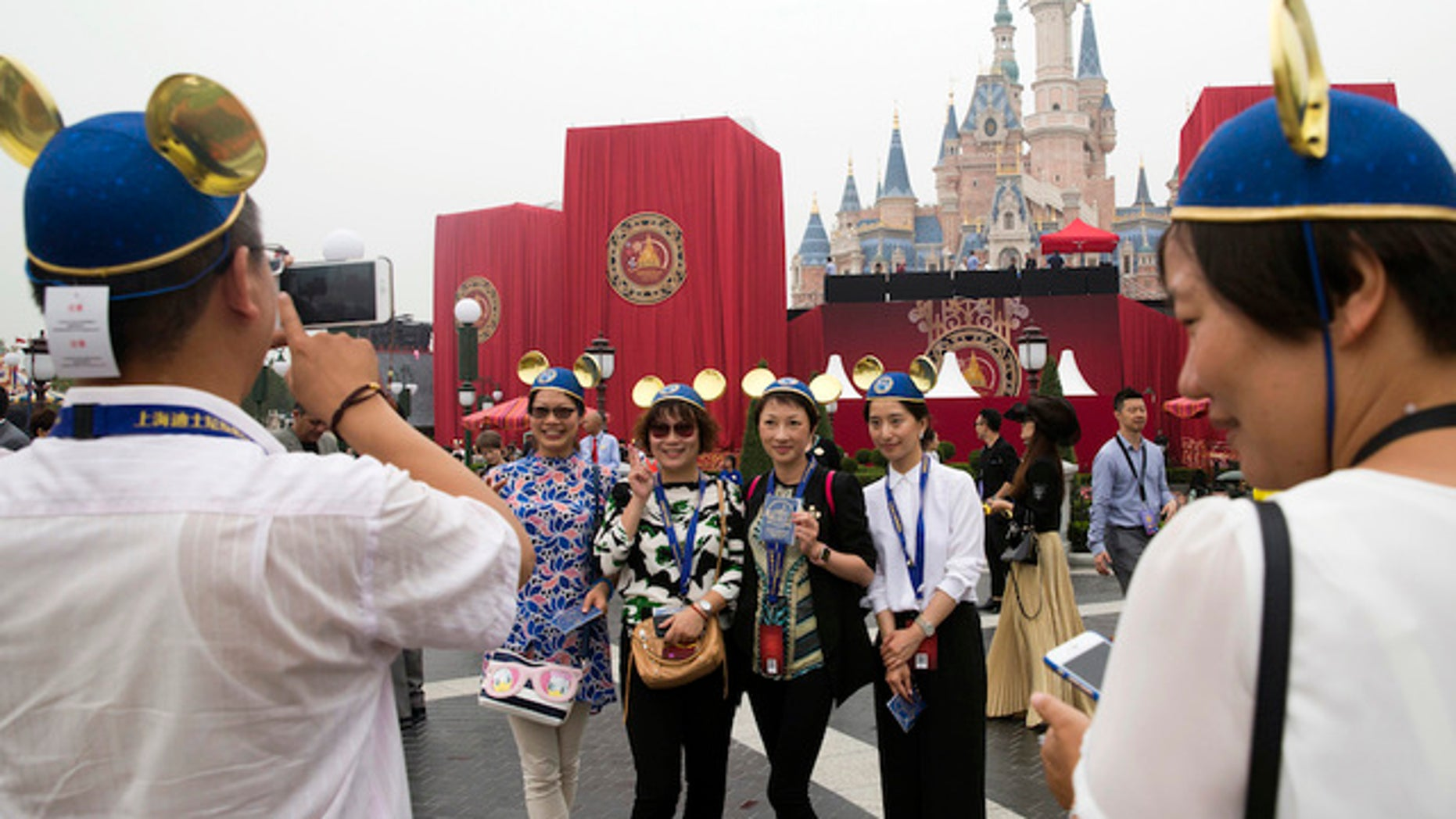 Guests strike pose on opening day at the newest Disney resort and theme park property in Shanghai, China.
