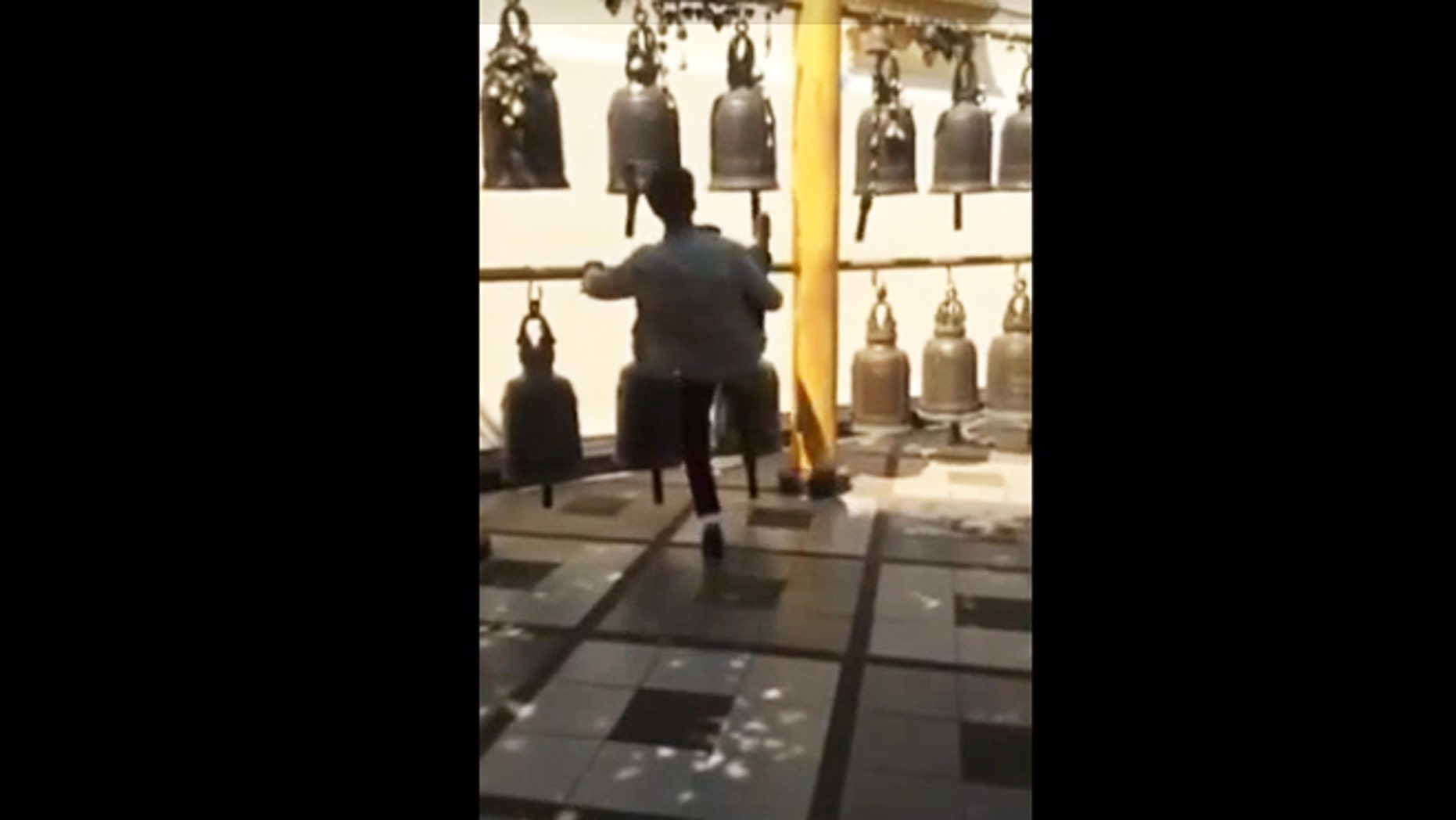 An unidentified tourist can be seen kicking a bell at the sacred Buddhist temple Wat Phra That Doi Suthep.