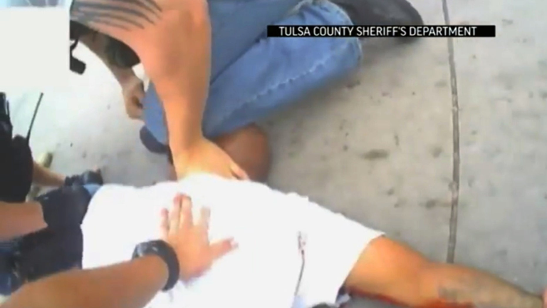 April 2, 2015: In this screen shot from a video provided by the Tulsa County Sheriff's Office, police restrain 44-year-old Eric Harris after he was chased down and tackled by a Tulsa County Deputy, and then shot by a reserve sheriff's deputy while in custody, in Tulsa, Okla.