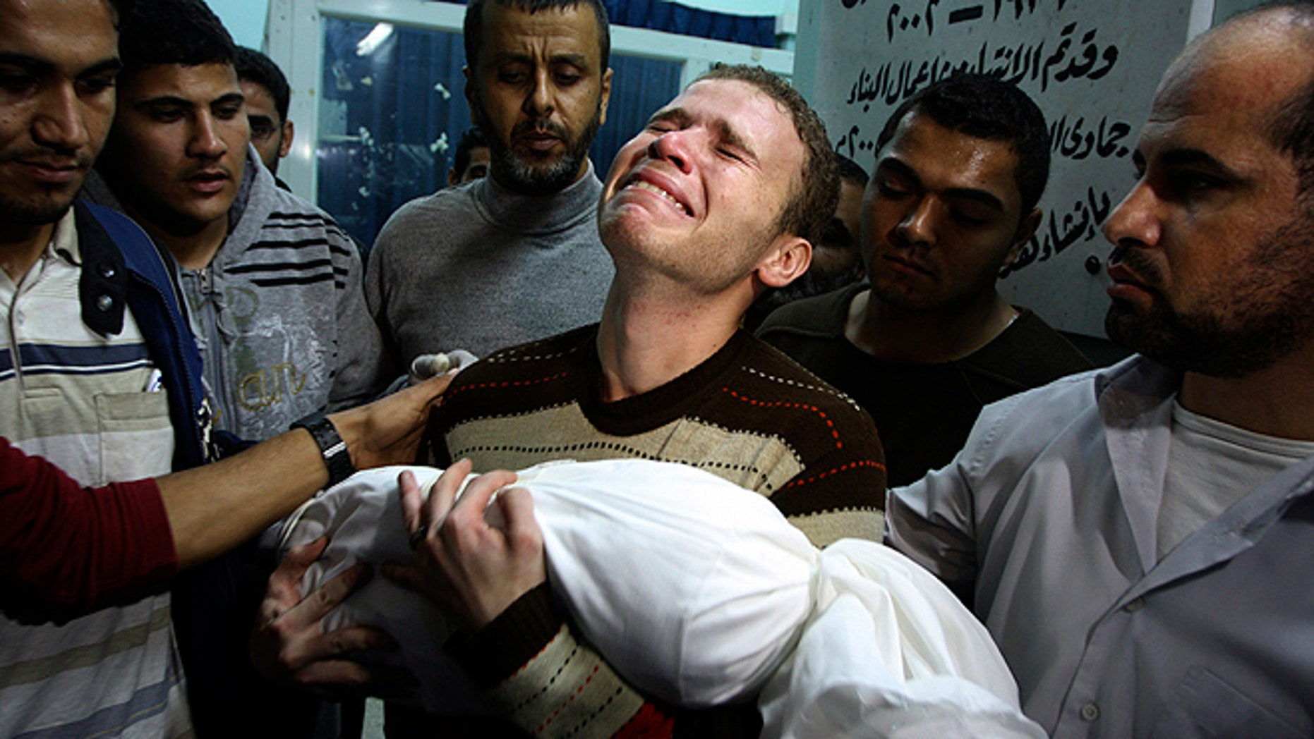 In this Nov. 14, 2012 file photo, an anguished Jihad al-Masharawi, a BBC reporter, clutches his slain 11-month-old son Omar in Gaza City. An errant Palestinian rocket, not an Israeli airstrike, likely killed the child during fighting in the Hamas-ruled territory, a U.N. report indicated, challenging the widely believed story behind the image which became a symbol of what Palestinians said was Israeli aggression. (AP)