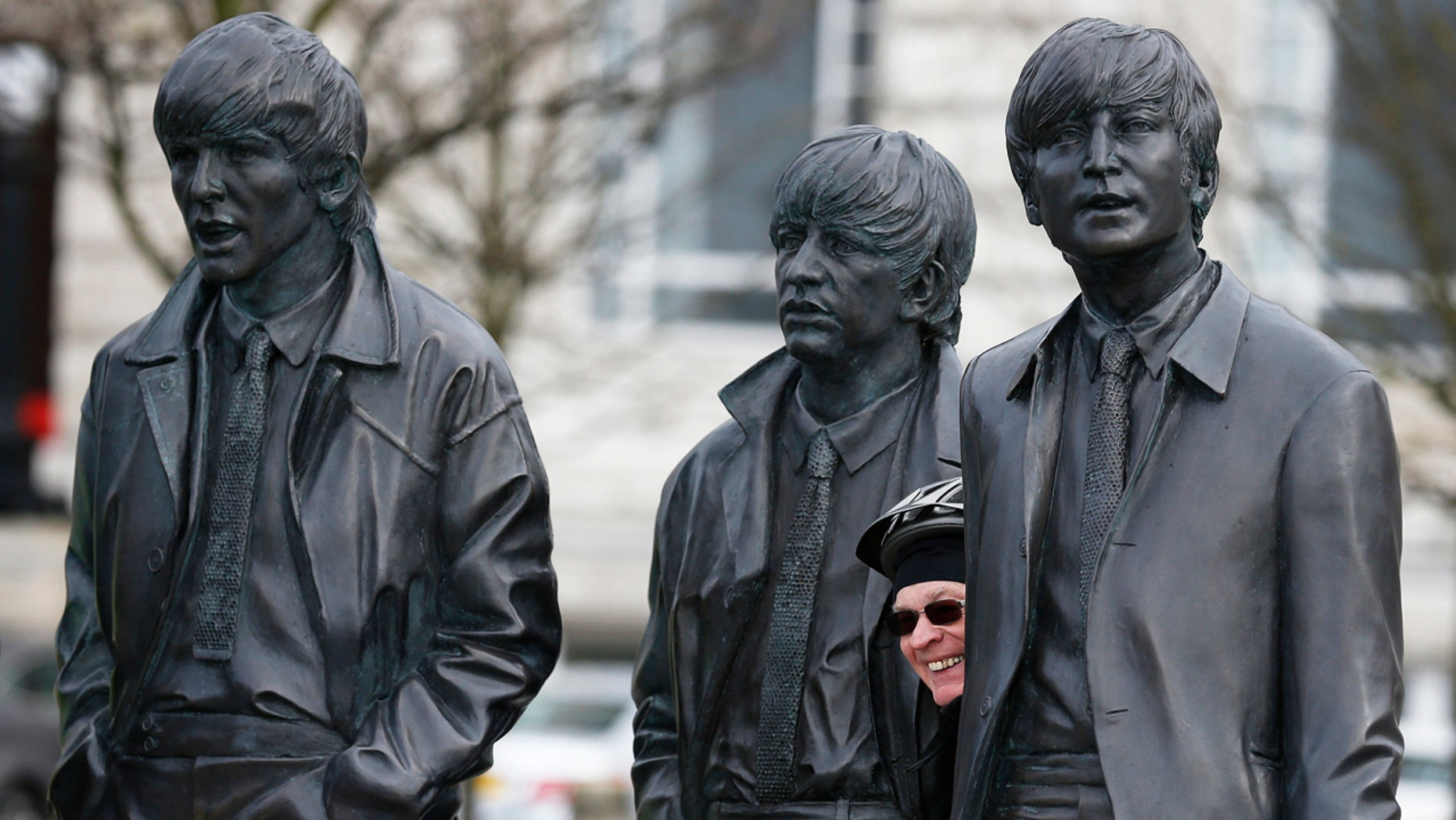 A fan poses next to a statue of The Beatles at the Pier Head in Liverpool, Britain March 9, 2016.