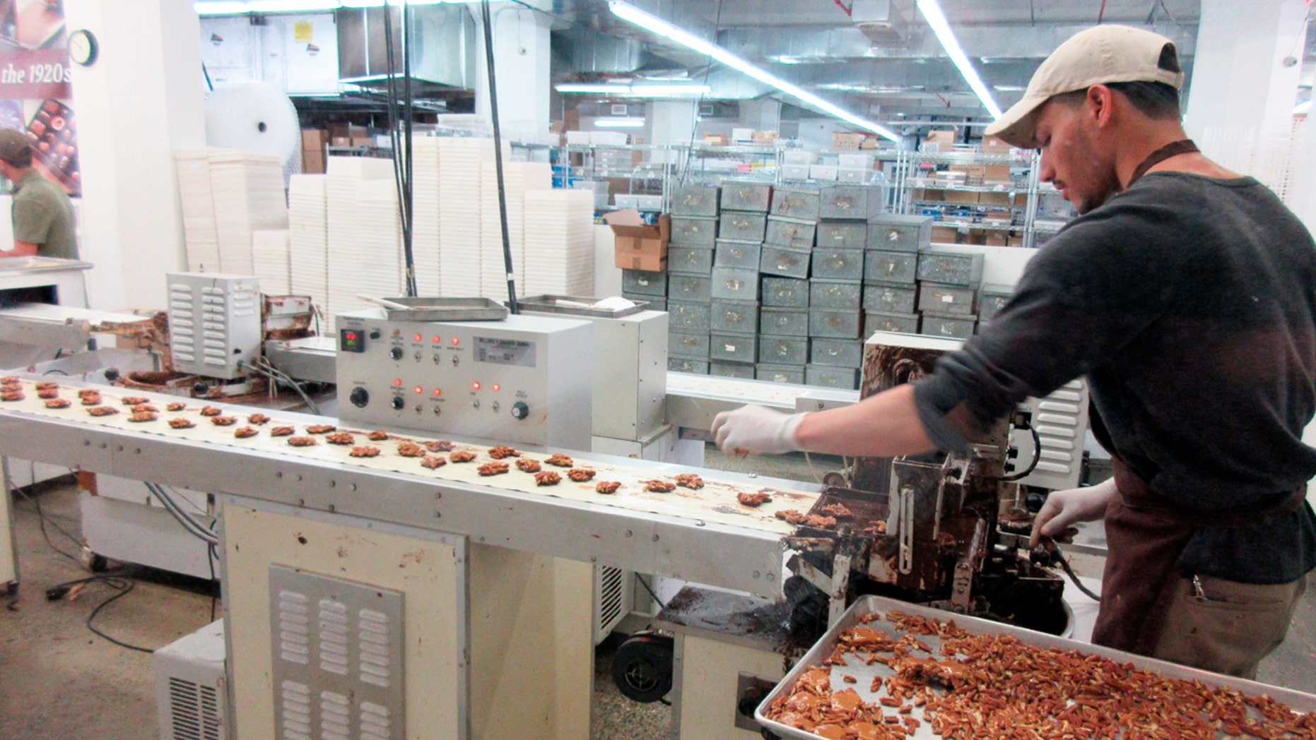 This April 28, 2017 photo shows a worker at Li-Lac Chocolates' factory in Industry City in Brooklyn, N.Y. Li-Lac is one of a number of stops on A Slice of Brooklyn chocolate tour, which offers chocolate samples to taste along with visits to different neighborhoods and insights into how some of the businesses on the tour got started. (AP Photo/Beth J. Harpaz)