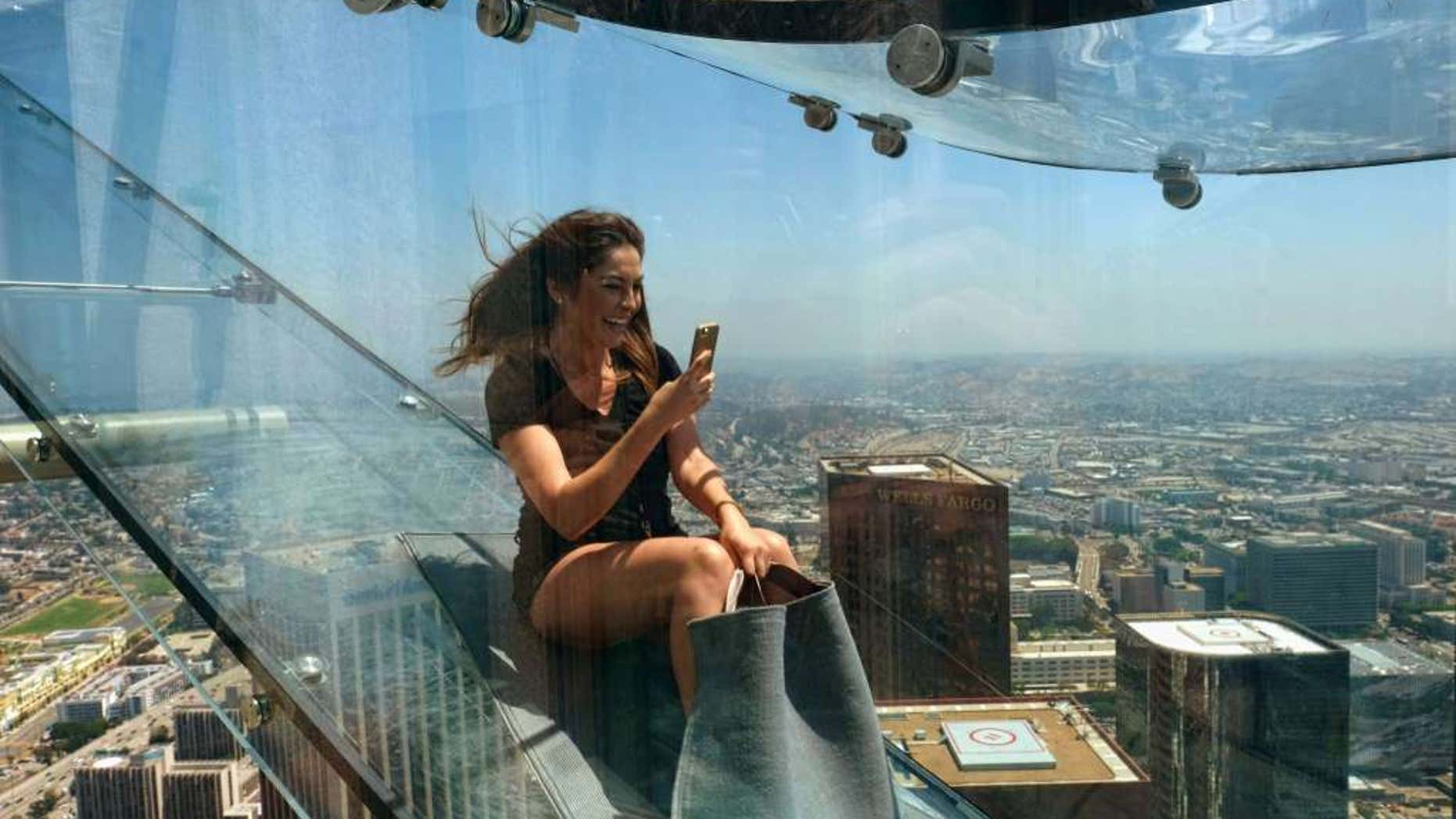 """Angela Cox a reporter with Seven Network Australia takes a photo with her phone as she takes ride down the U.S. Bank Tower building's 1,000 foot tall """"Skyslide"""" in downtown Los Angeles on Thursday, June 23, 2016."""