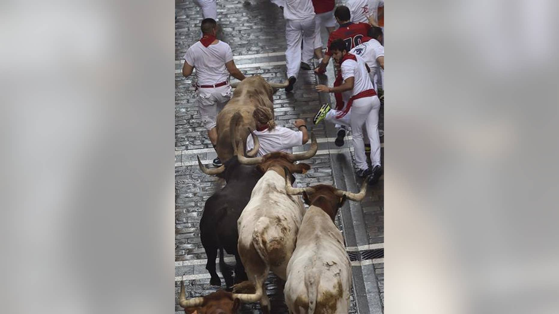 A runner runs in front Fuente Ymbro fighting bulls on the Estafeta street during the first running of the bulls at the San Fermin Festival, in Pamplona, Spain.