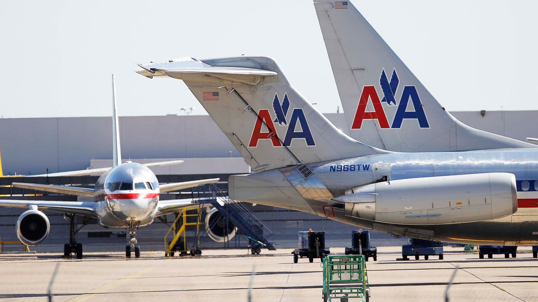 American Airlines airplanes pass by a hanger at Dallas/Fort Worth International Airport.