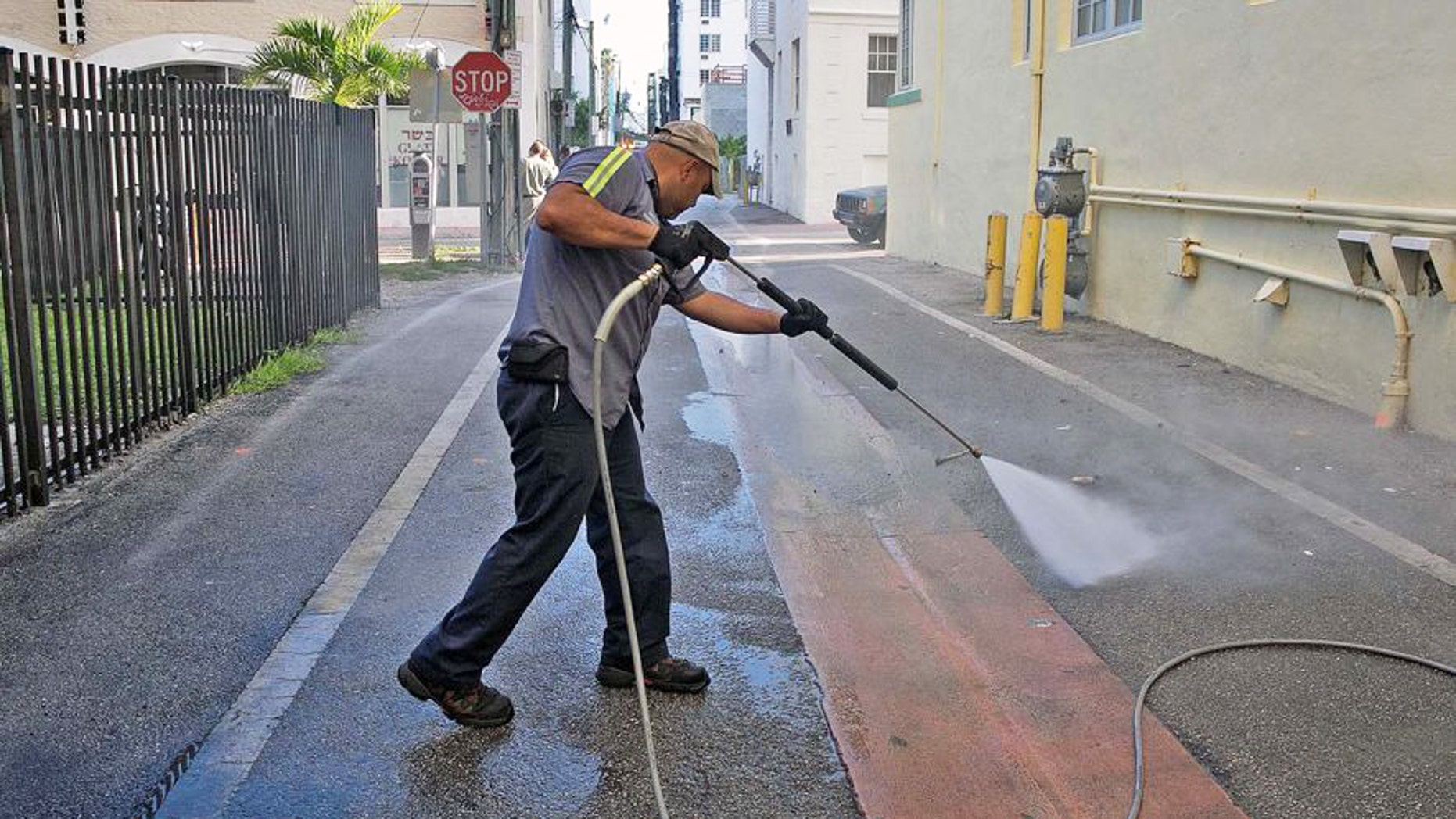 A worker washes down alleyways in Miami Beach. Travel insurer Allianz is predicting a 15 percent drop in Florida travel amid Americans' heightened fear of the Zika virus.