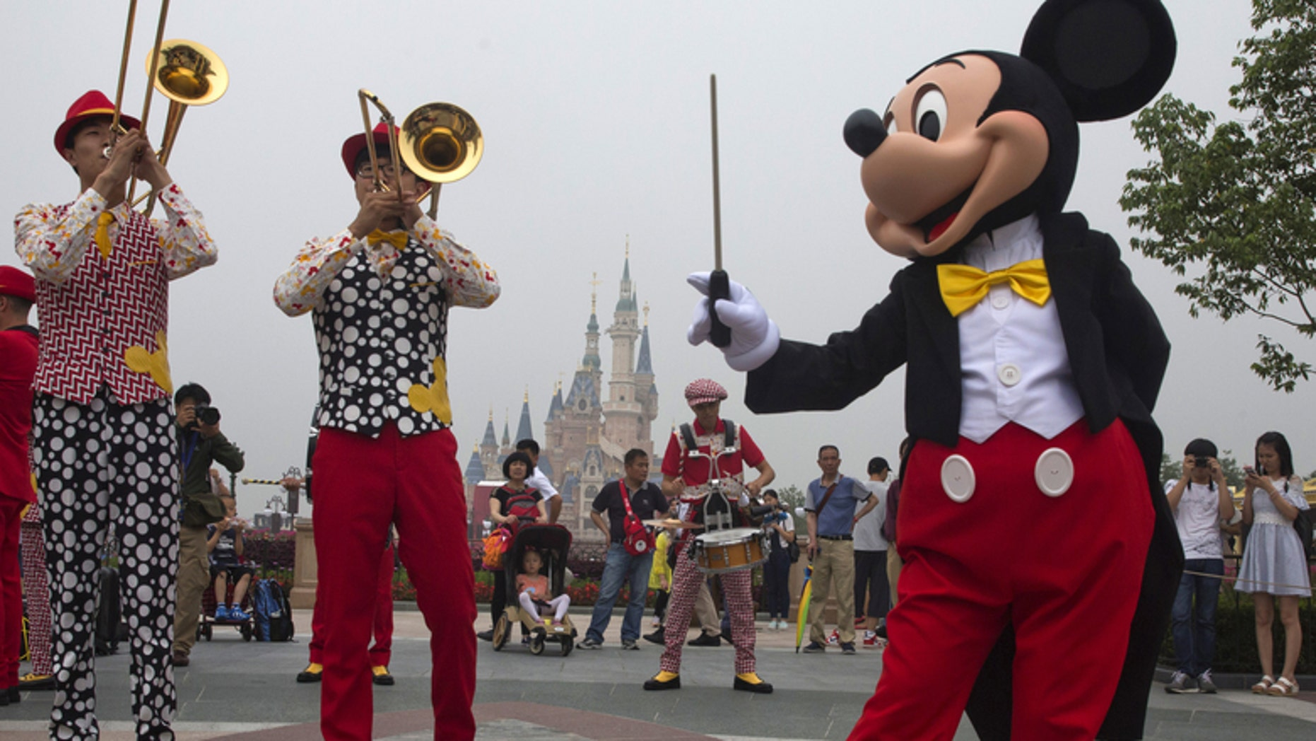 Mickey Mouse entertains onlookers on the rainy day opening of Shanghai Disney Resort.