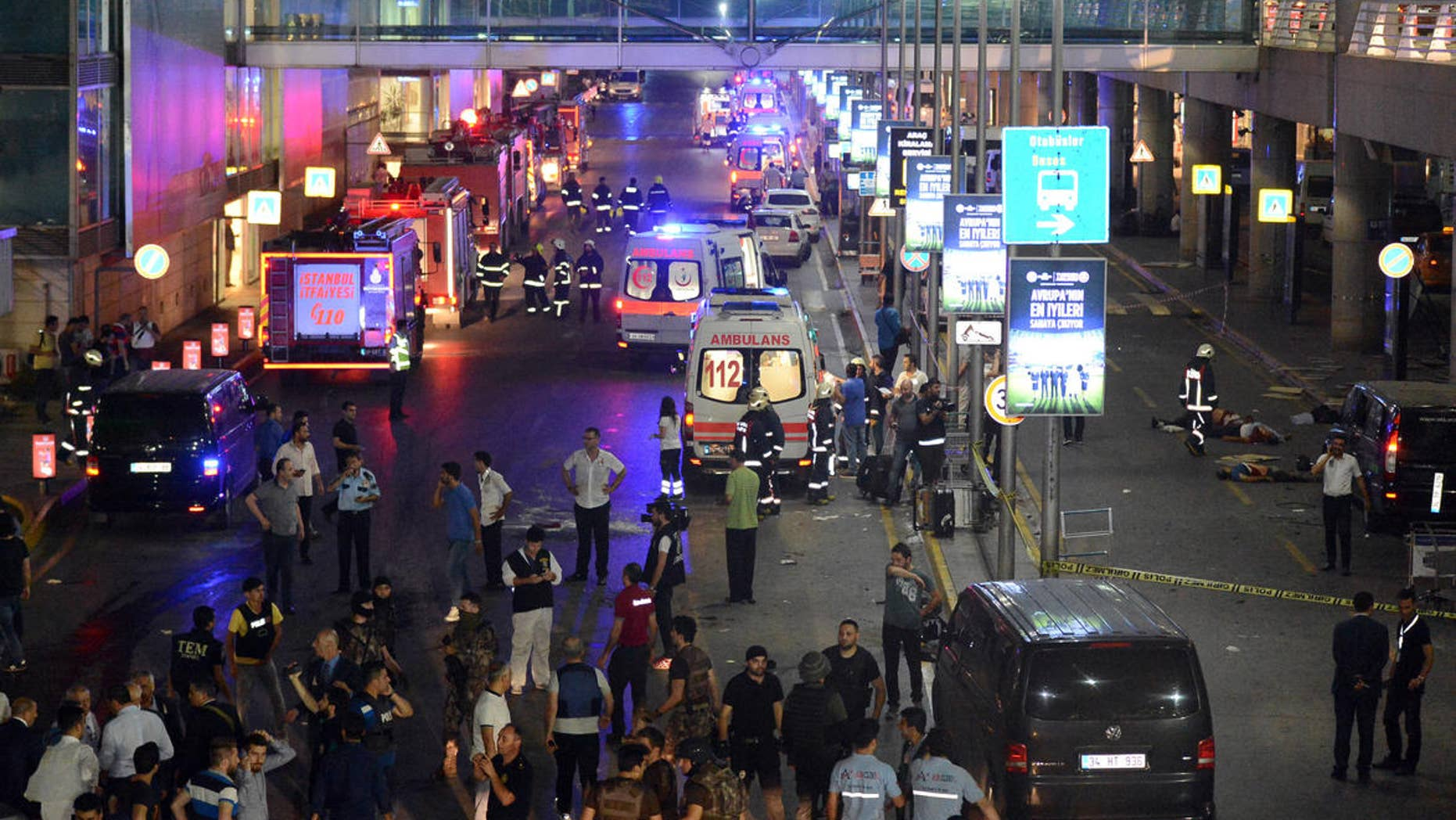 Medics and security members work at the entrance of the Ataturk Airport after explosions in Istanbul, Tuesday, June 28, 2016.